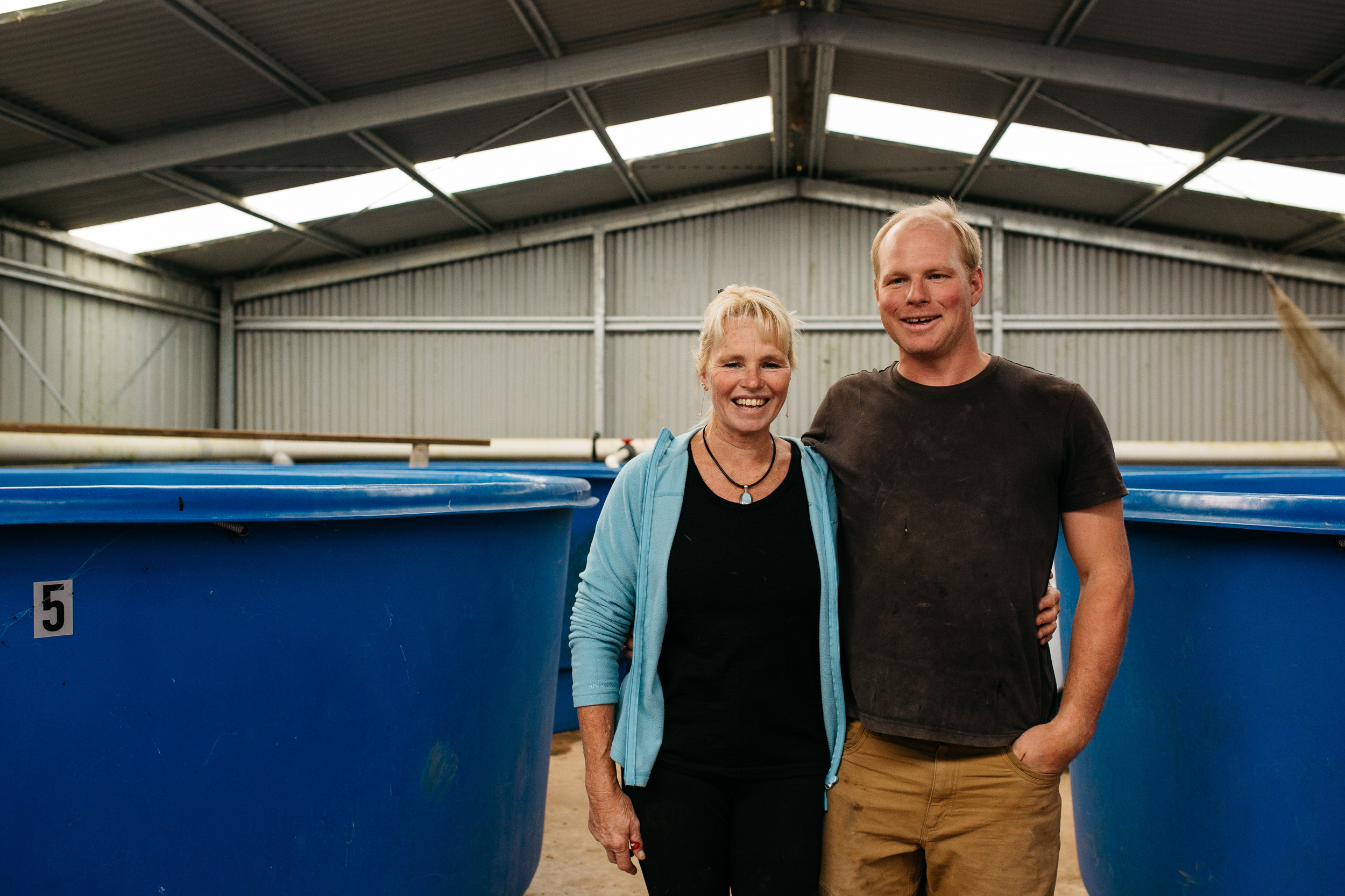Sally Hall with her son David and fish tanks in the background, Mountain Fresh Trout and Salmon Farm, Harrietville (Victoria), 2017, Photographer: Catherine Forge, Source: Museums Victoria.