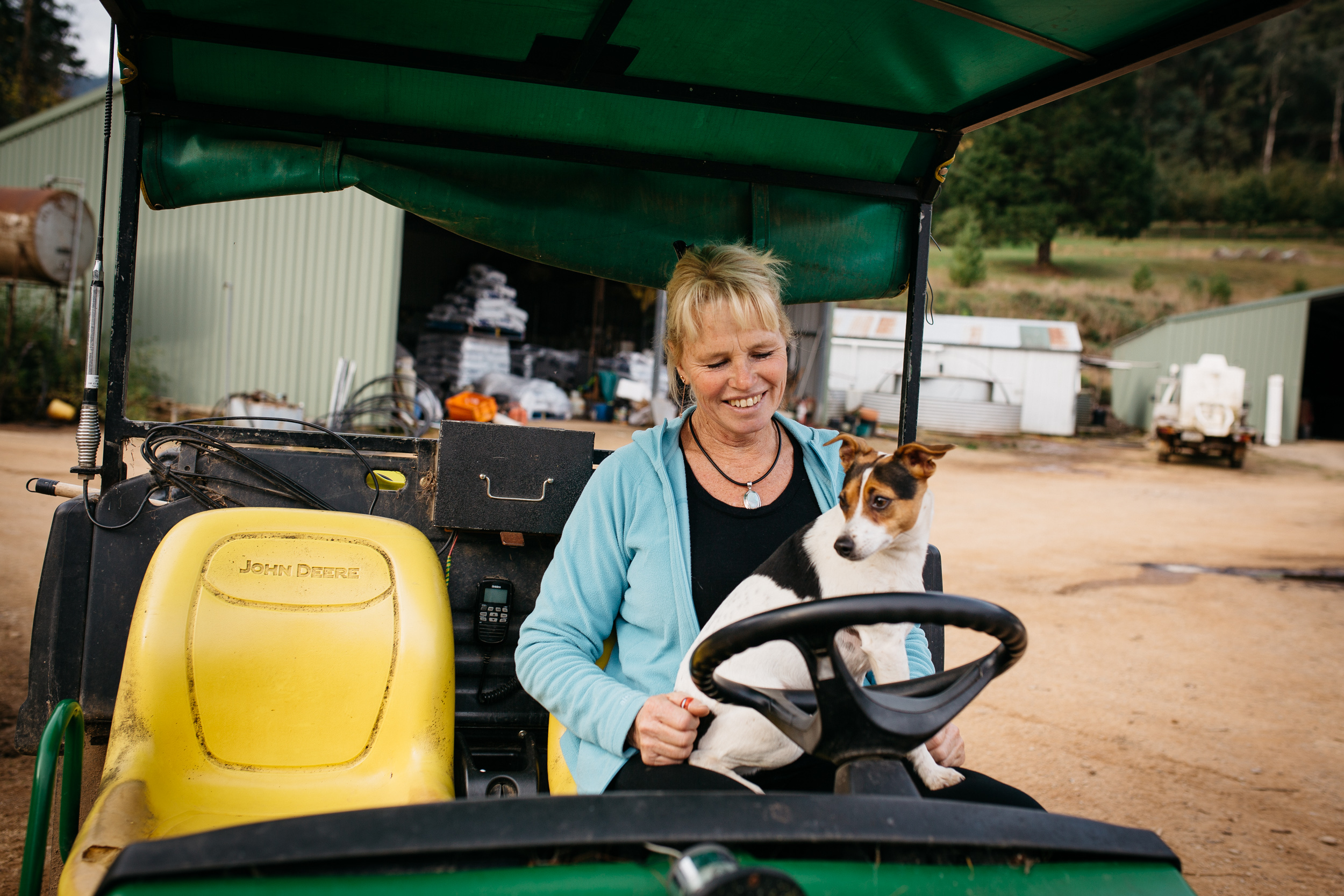 Sally Hall with her dog on a John Deere utility vehicle, Mountain Fresh Trout and Salmon Farm, Harrietville (Victoria), 2017, Photographer: Catherine Forge, Source: Museums Victoria [MM 145577:  https://collections.museumvictoria.com.au/items/2241617 ].