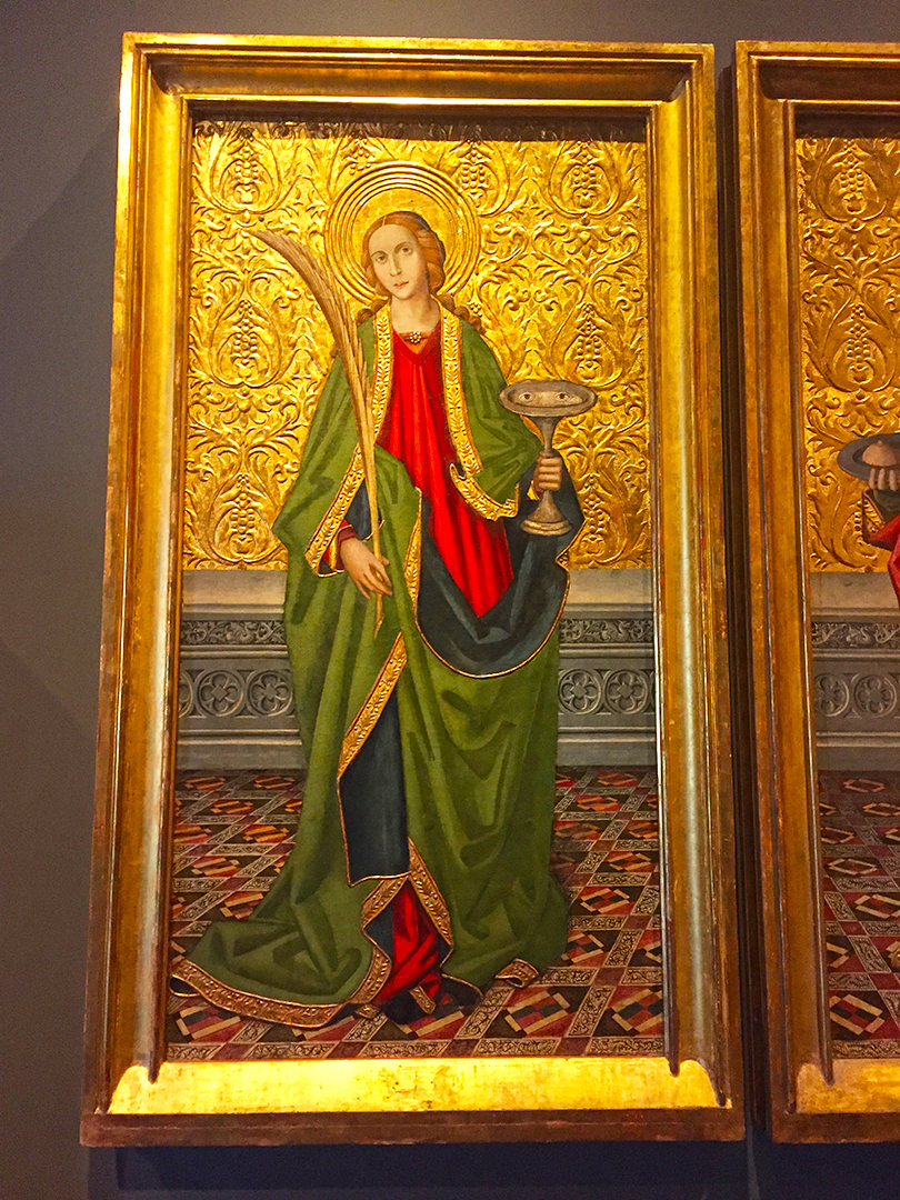 """Saint Lucy, Vergós Workshop, Spanish, about 1500, Oil and gold on panel. They were Roman-Sicilian martyrs and St. Lucy hold her attribute, eyes on a dish. This photo does not do this image justice ... the gold is thick and has mass like an emboss and her green cloak is still vibrant, as if it was created just recently. This artwork can be found in the new, impressive exhibition space, """"The Deering Family Galleries of Medieval and Renaissance Art, Arms & Armor"""". Well worth the visit to the museum!"""