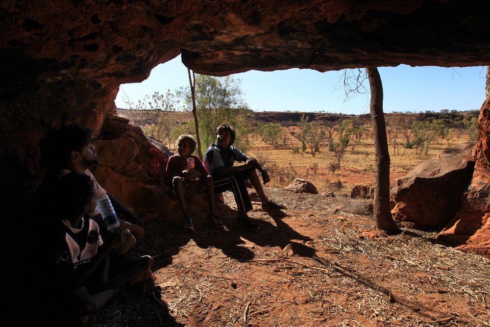 Louis and three of his students take refuge from the sun in one of the red sandstone caves that flank the edges of Kings Creek in Watarrka National Park in Australia's Northern Territory.