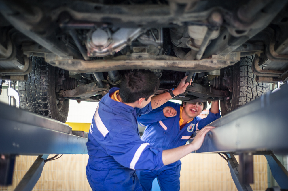 Two of Jose Luis's students explore the underside of a car.
