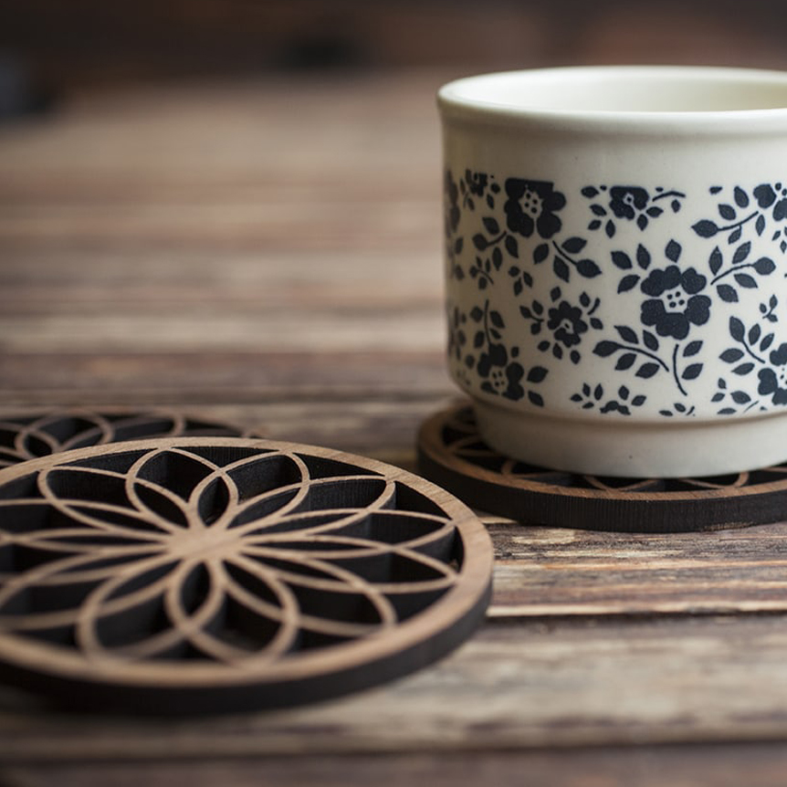 "Flower Of Life - A set of 4 boxed ""Flower Of Life"" coasters in 6mm thick American Black Walnut, featuring a beautiful floral geometric pattern. Each coaster is laser cut, hand sanded and oiled for protection.£25.00 for 4Available at www.denvers.com"