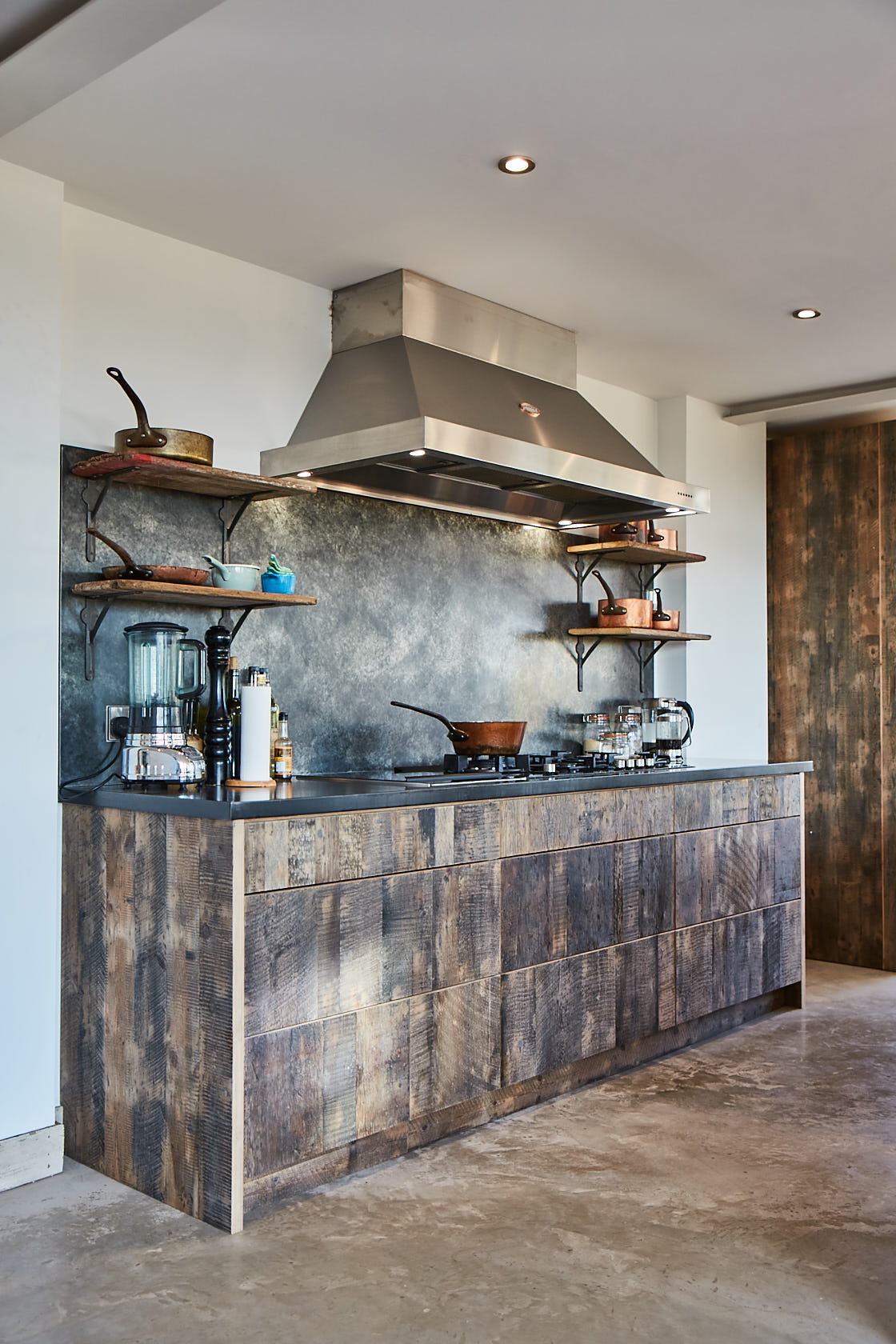 natural textures - If colour isn't really your thing, think about introducing natural materials into your kitchen. This kitchen by The Main Company features a reclaimed engineered pine wood finish of Oldham Mill Board, solid oak drawer boxes and lacquered birch plywood carcasses. Much in the same way that Diane Keaton designed her home, this kitchen contrasts industrial greys and urban fittings with the natural texture of reclaimed wood breakfast bar to create a rustic, stylish space. This is a perfect example of how to create a unique space by using neutral tones. This simple twist on the traditional kitchen styles makes for a kitchen that will only improve with age.