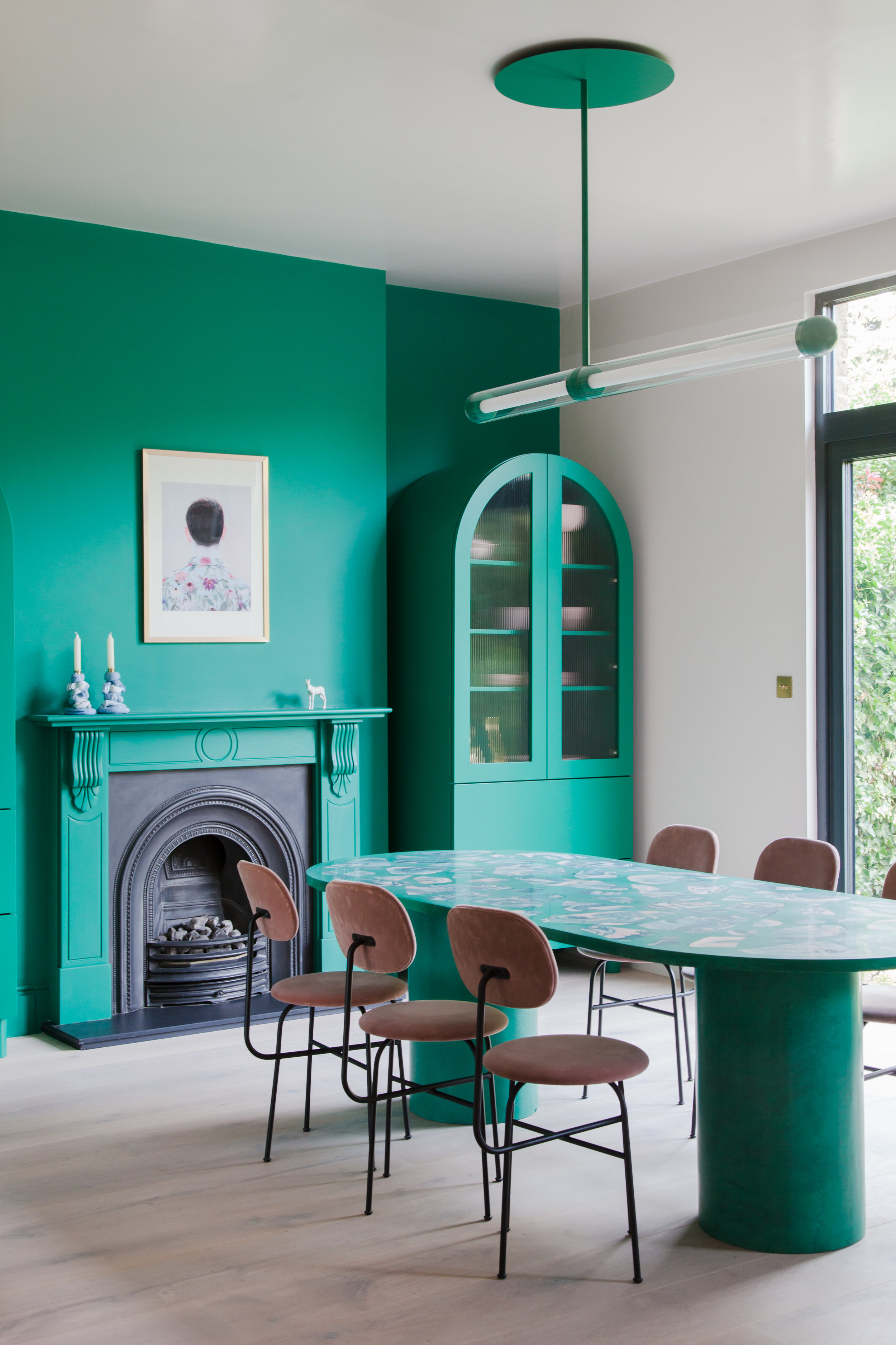 - As a contrast to the pale tones in the kitchen, the dining area is unapologetically bold, with vibrant green paint from Mylands used on the back wall and matched by freestanding larder units. In the middle of the room, the distinctive Jesmonite dining table by surface designer Olivia Aspinall brings the space together, combining that statement shade of green with accents of pink and tonal teal. We're also obsessed with those Menu dining chairs!Image credit: Megan Taylor Photography for John Lewis of Hungerford