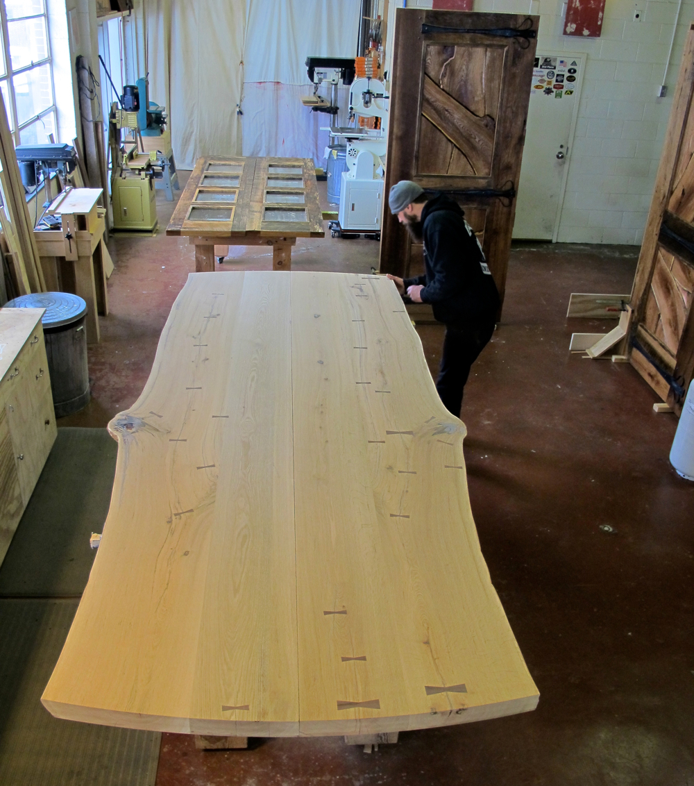 Large Live Edge Slab Dining Table - Working out the details. Pouring epoxy for a perfect finish and determining the width of the open seam down the middle to allow for movement. Wood moves throughout it's entire life and it's our job to allow for this without damaging the furniture.