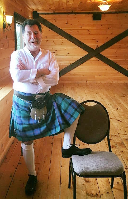 Bruce in his Highland dancing regalia at his son and daughter-in-law's wedding, August, 2016. (Image: A dark-haired, white-bearded man in a blue plaid kilt, cream-coloured shirt and stockings standing casually while smiling warmly.)
