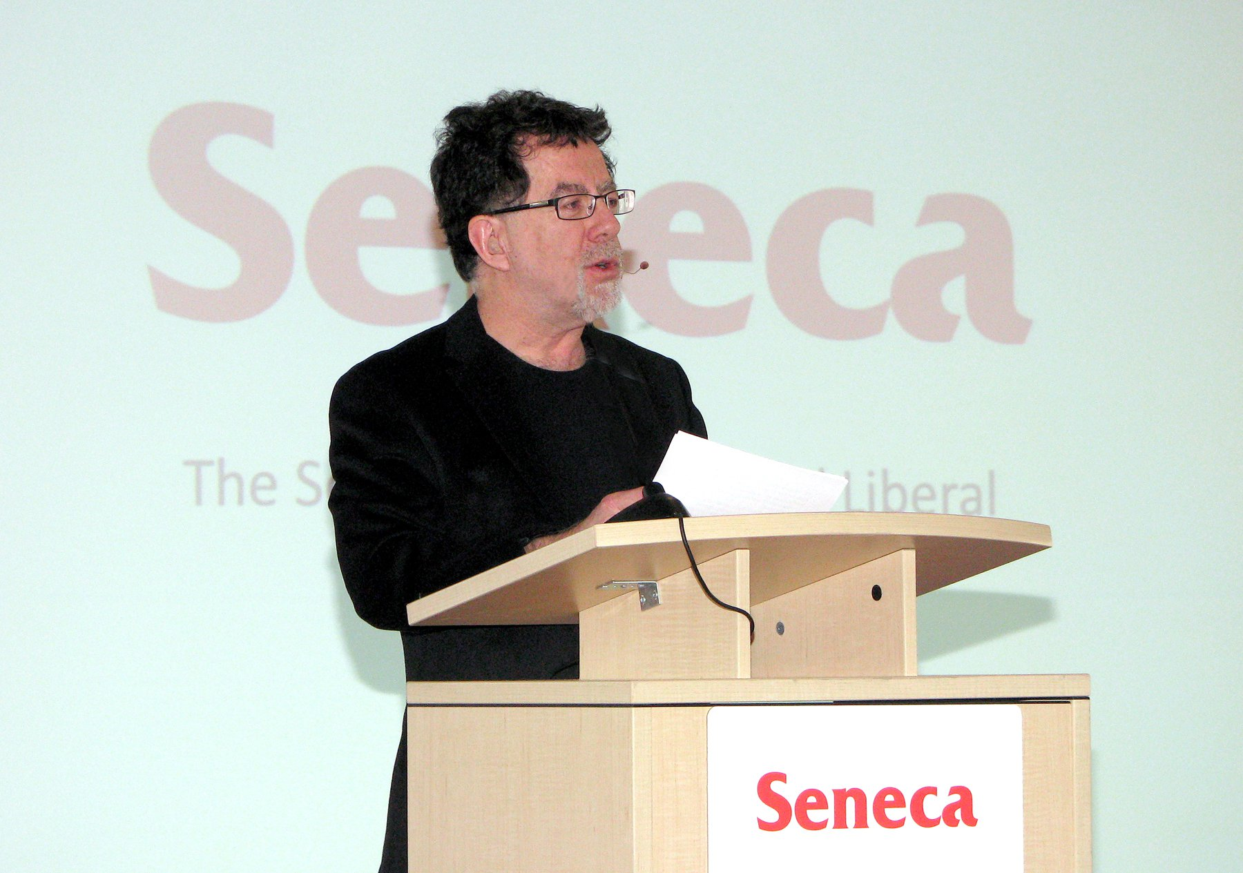 """Bruce's keynote presentation: """"Reading Minds, Not Lips"""" 2011, English and Liberal Studies Colloquium. Seneca College. (Image: A brown-haired man speaking into a headset mic from a podium against a white background that says Seneca.)"""