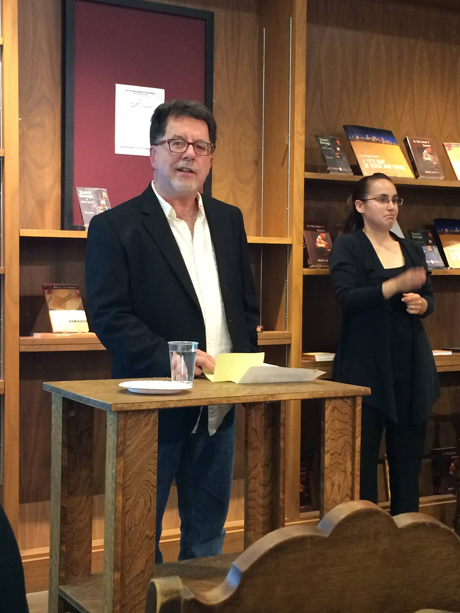 Bruce mcing a literary kitchen party at Shelf Life Books, 2014 with ASL-interpreter and a captioner (off camera). (Image: A dark-haired man in glasses wearing a dark sports jacket at a podium beside a young woman signing for the audience. In th background are books on display.)