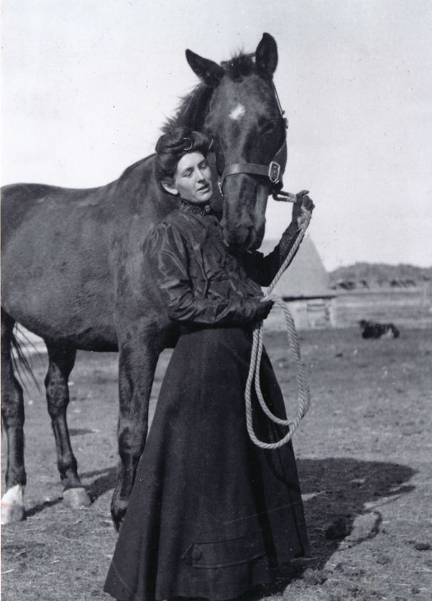 From the Glenbow Archives (Image: A young woman holding a loop of halter rope while being nuzzled by her black horse which has a white blaze between its eyes. She is wearing a long black riding skirt, dark high-necked blouse and black gloves. In the background is a barn and corral.)