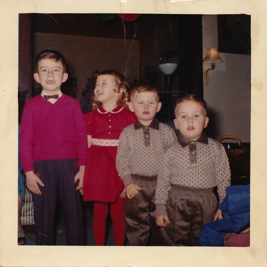 1960 Bruce aged six in a bow tie and red sweater, sister Susan aged five in a red dress, brothers Michael aged four and Allan aged three. (Image; Four children, three boys and one girl all dressed in Christmas garb and the two youngest boys are wearing matching outfits of patterned shirts and shiny pants. The girl is smiling up at her older brother who is missing two front teeth.)