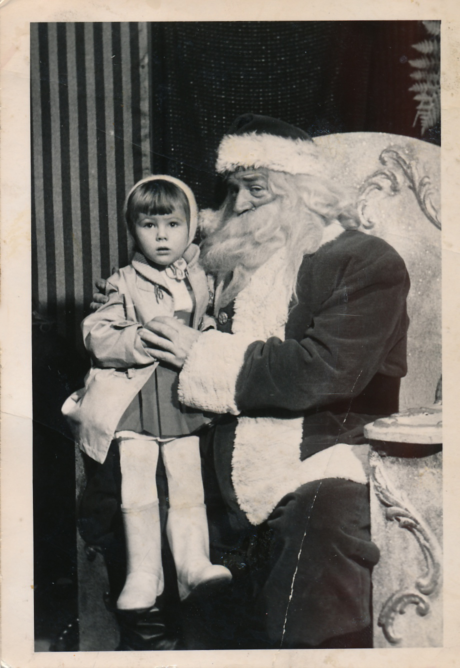(Image: A young girl in winter hat and coat with white leotards and white boots sitting on Santa's lap.)