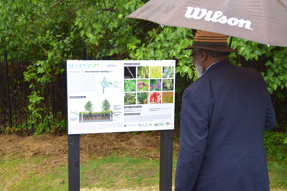 A board member of the PNBC Community Development Corporation learns about rain gardens
