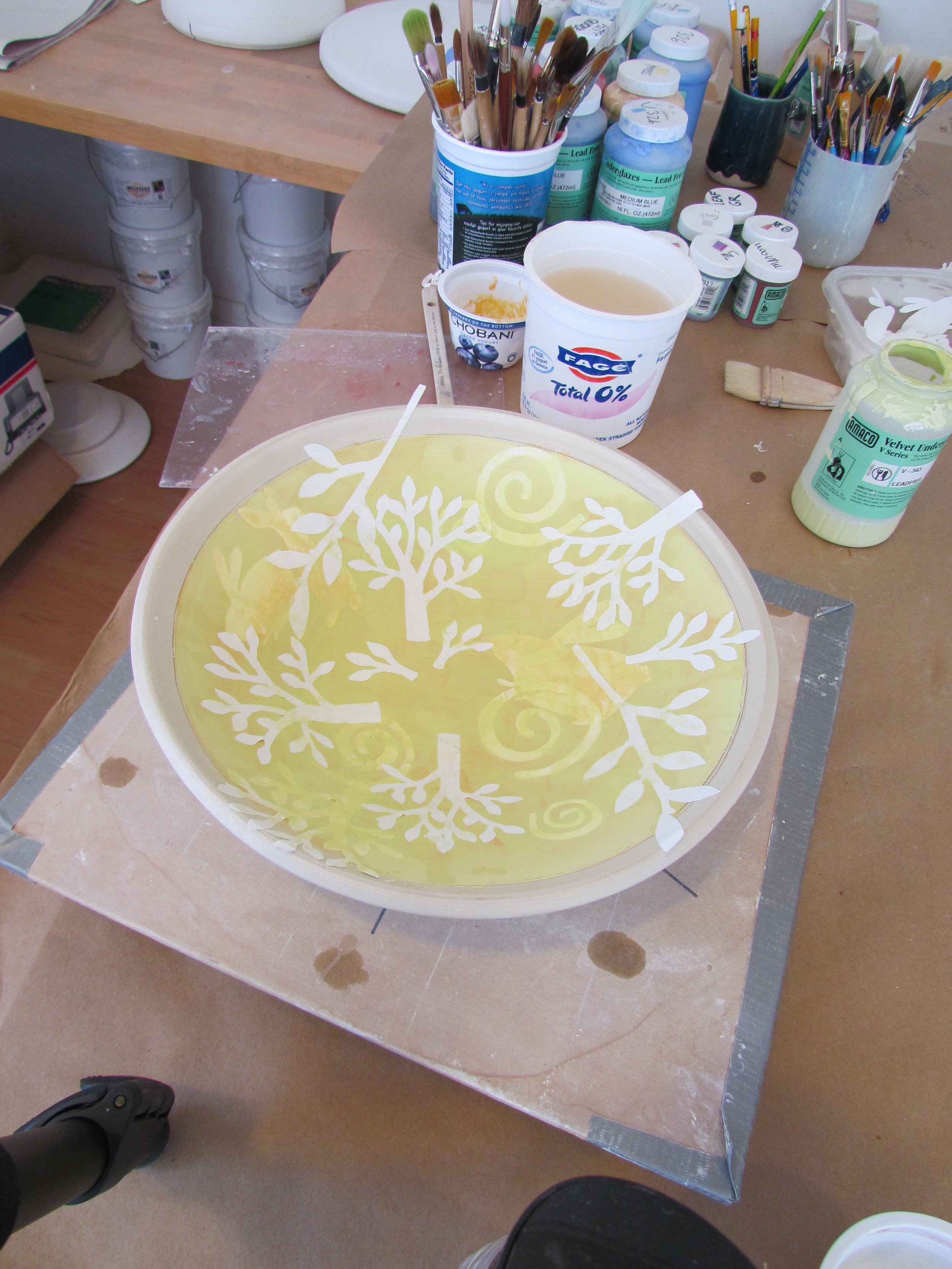 A new color of underglaze is selected( in this case chartreuse ) and applied over the second layer of stencils