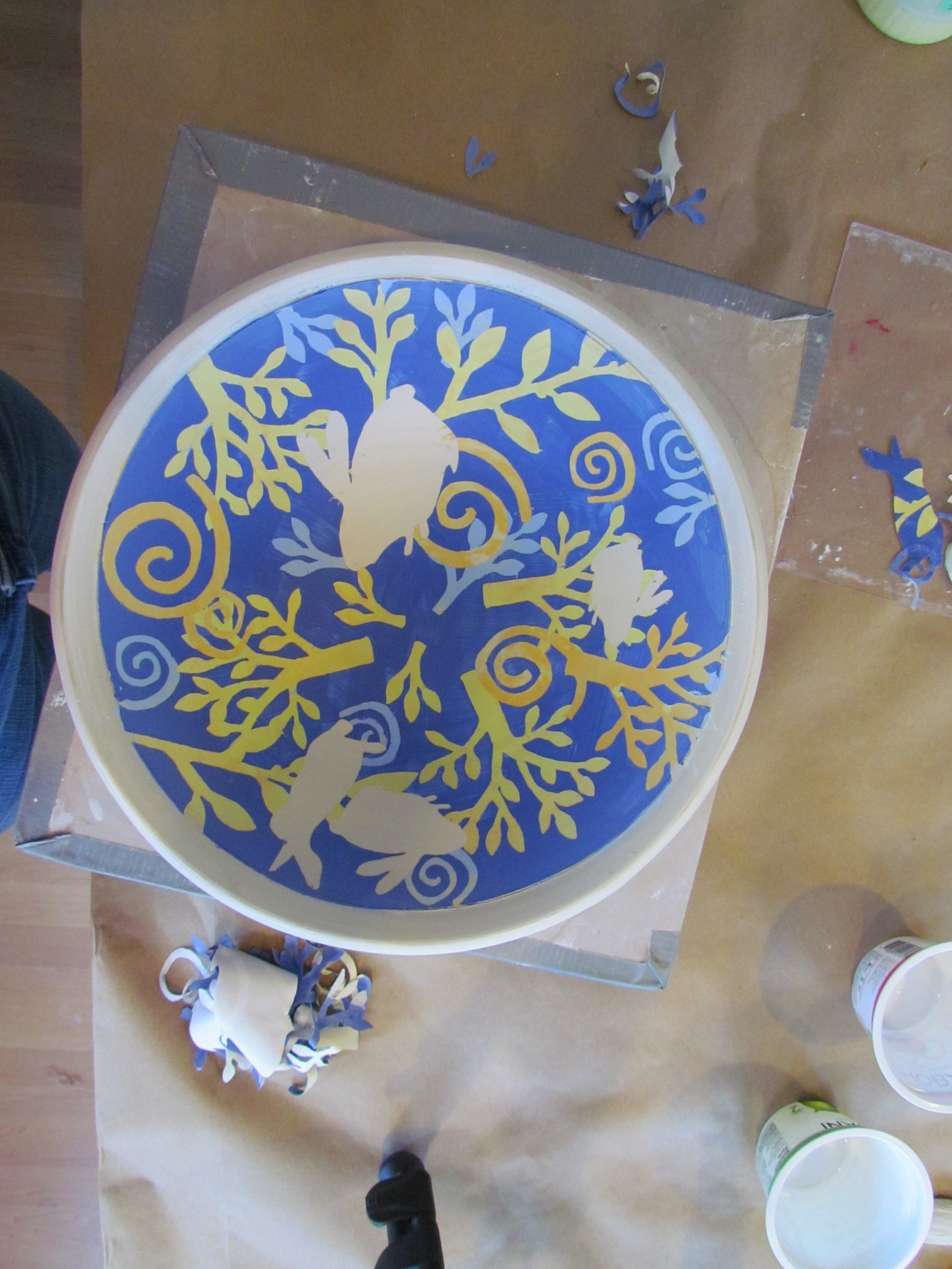 Once the final layer of underglaze has dried (in this case navy blue), all of the paper stencils are removed to reveal multiple layers of colors.   The piece is then fired in a kiln to 1940 degrees F . After this firing, the bowl will be painted with clear glaze and fired a second time to 2232 degrees F.