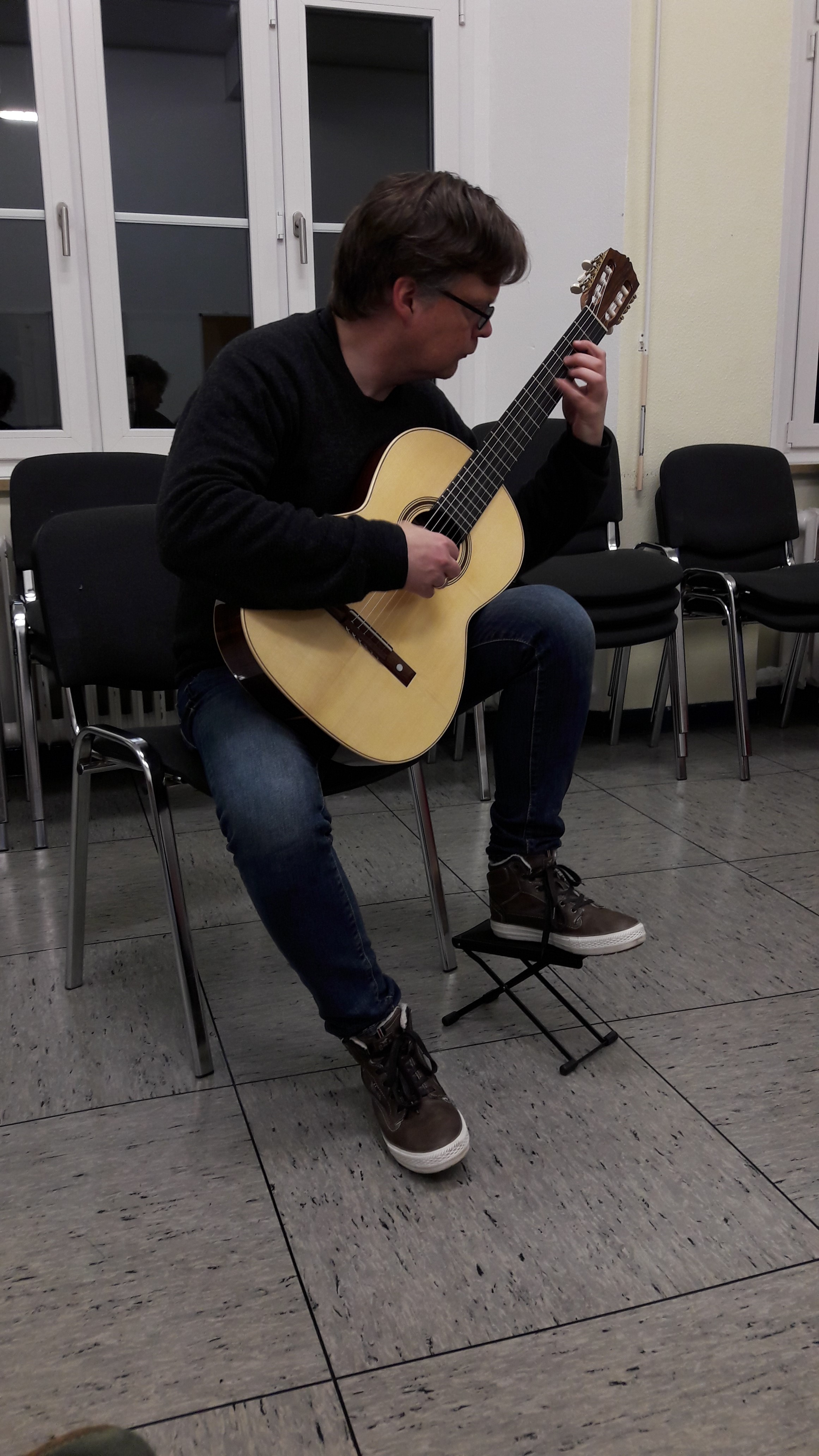 Dominik Jung, guitar teacher in Siegen trying out Den Toom Luthier guitar in Rosewood.