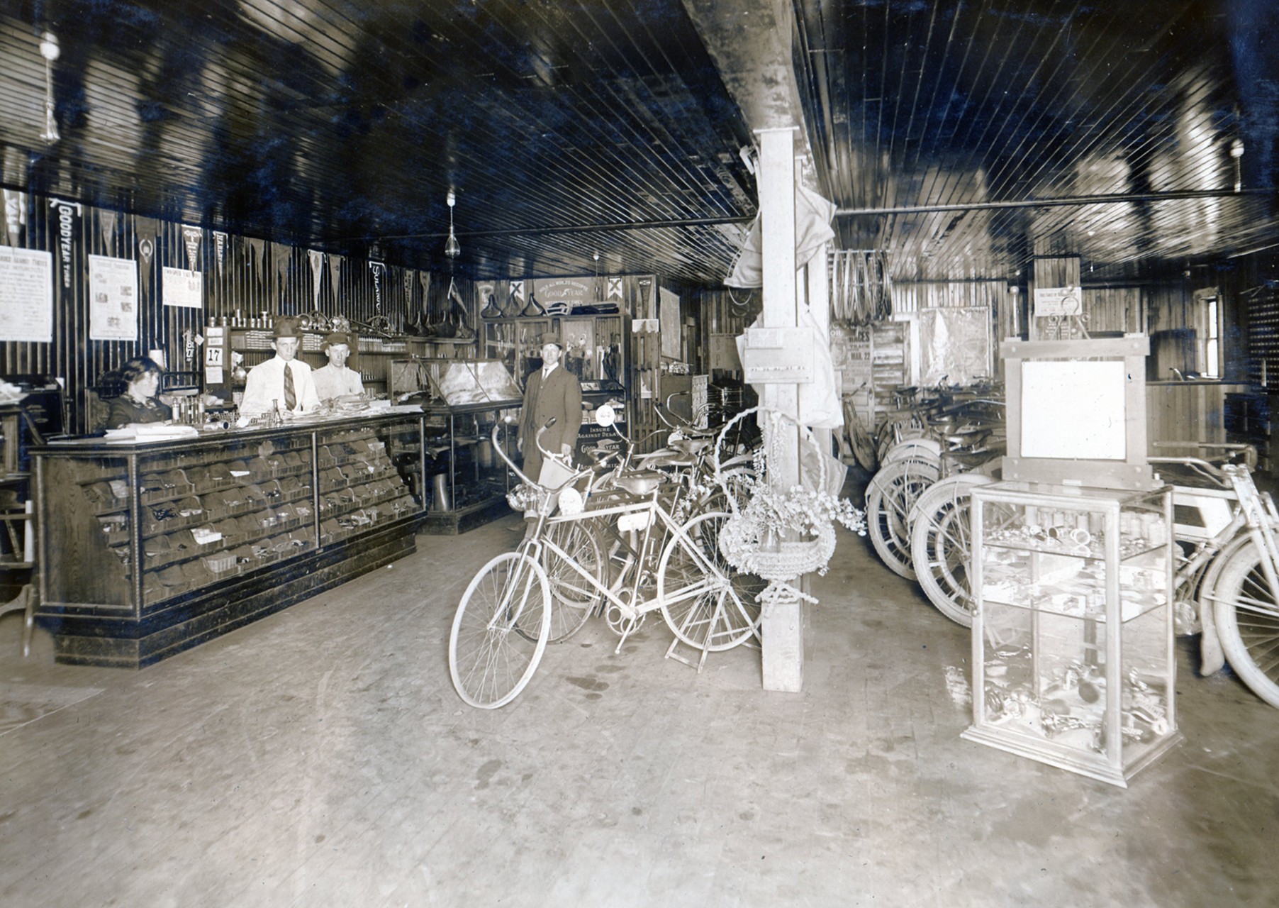 A very rare shot of the inside of Langley's dealership. Equal space was given to motorcycles and bicycles with ample room for parts and accessories. Langley stands outside the counters near the center of the picture.
