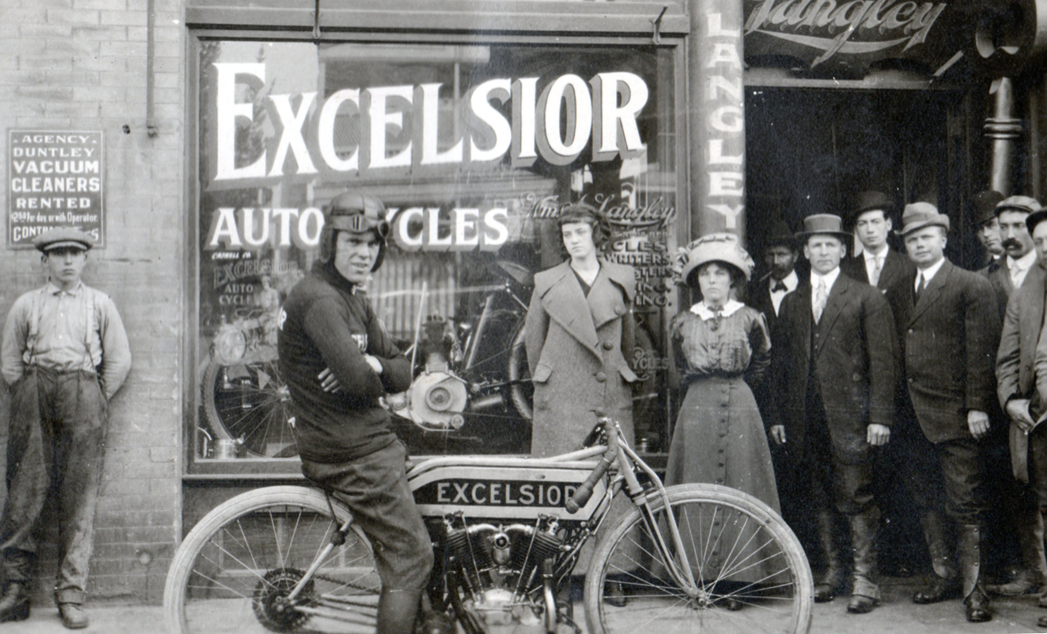 A very serious Bob Perry posing with his factory racer in front of Langley's shop in 1913. Langley stands third from the left in the main group standing next to Elma.