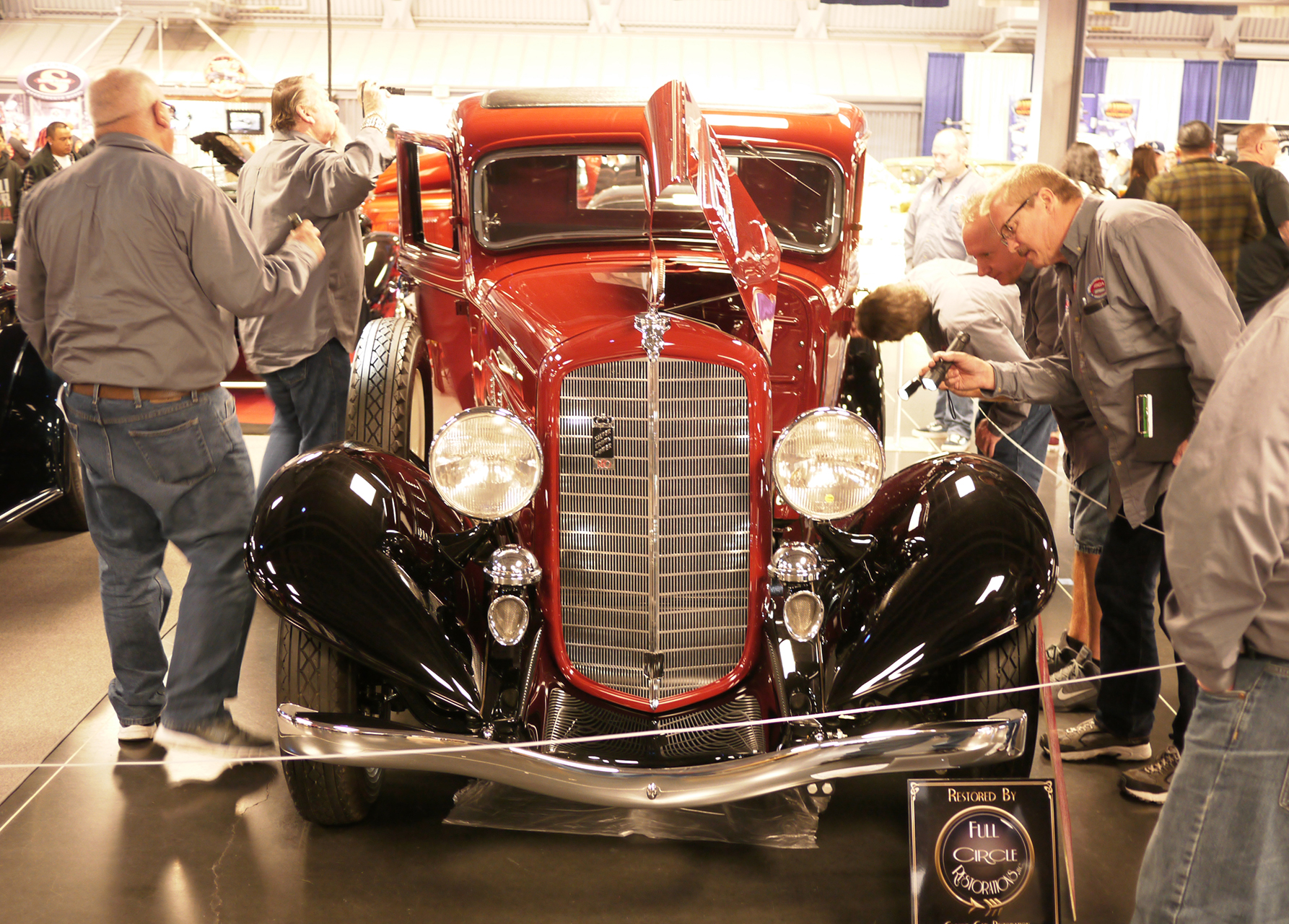 The judging crew gives a REO pickup a thorough going over. That's Ransom E. Olds thank you.