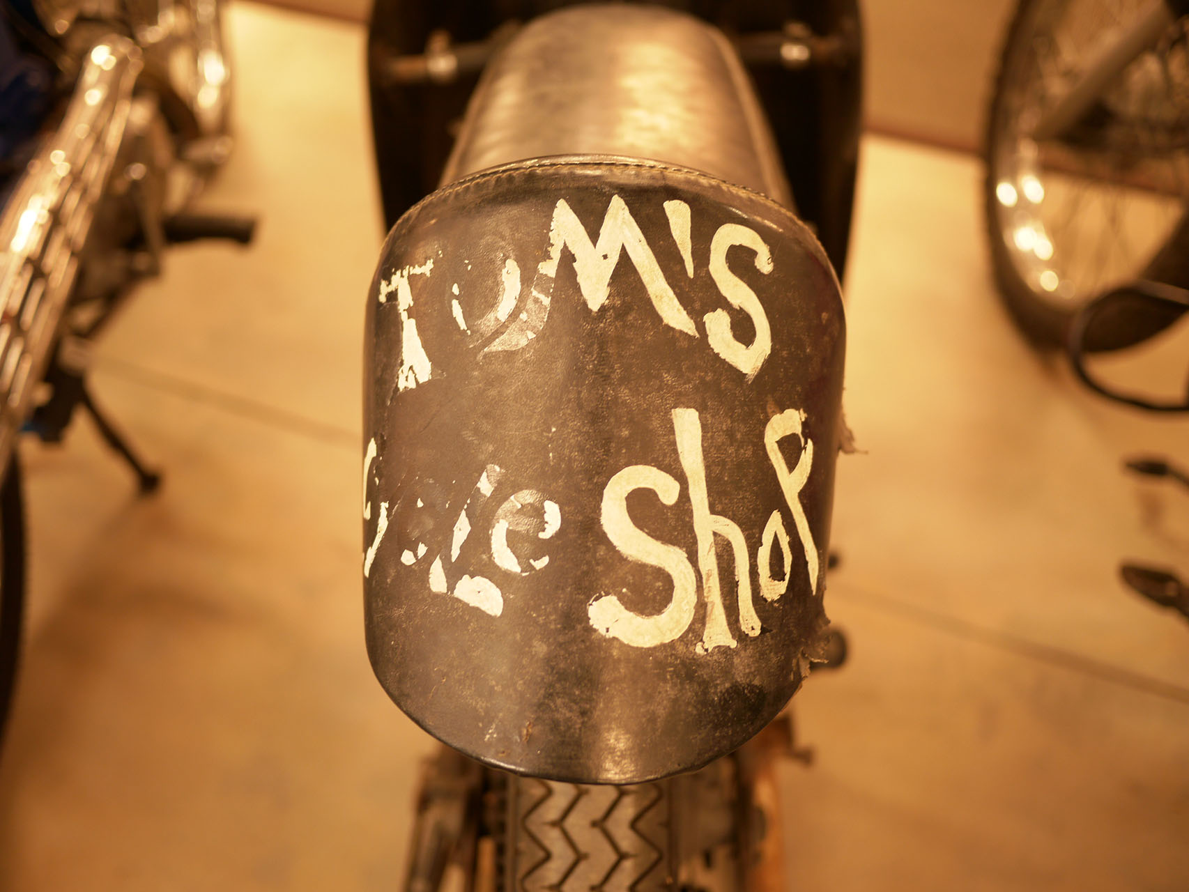 """fantastic patina on the Tom's Bike Shop Steen Aermacchi/Hodaka road racer. It is great that the collection is willing to let bikes have their history. It would be a crime to """"restore"""" this bike."""