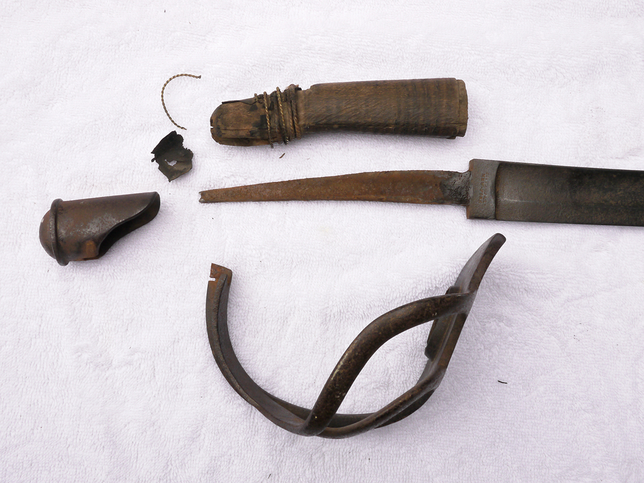The disassembled parts of the hilt. Everything is dirty but in good shape otherwise.