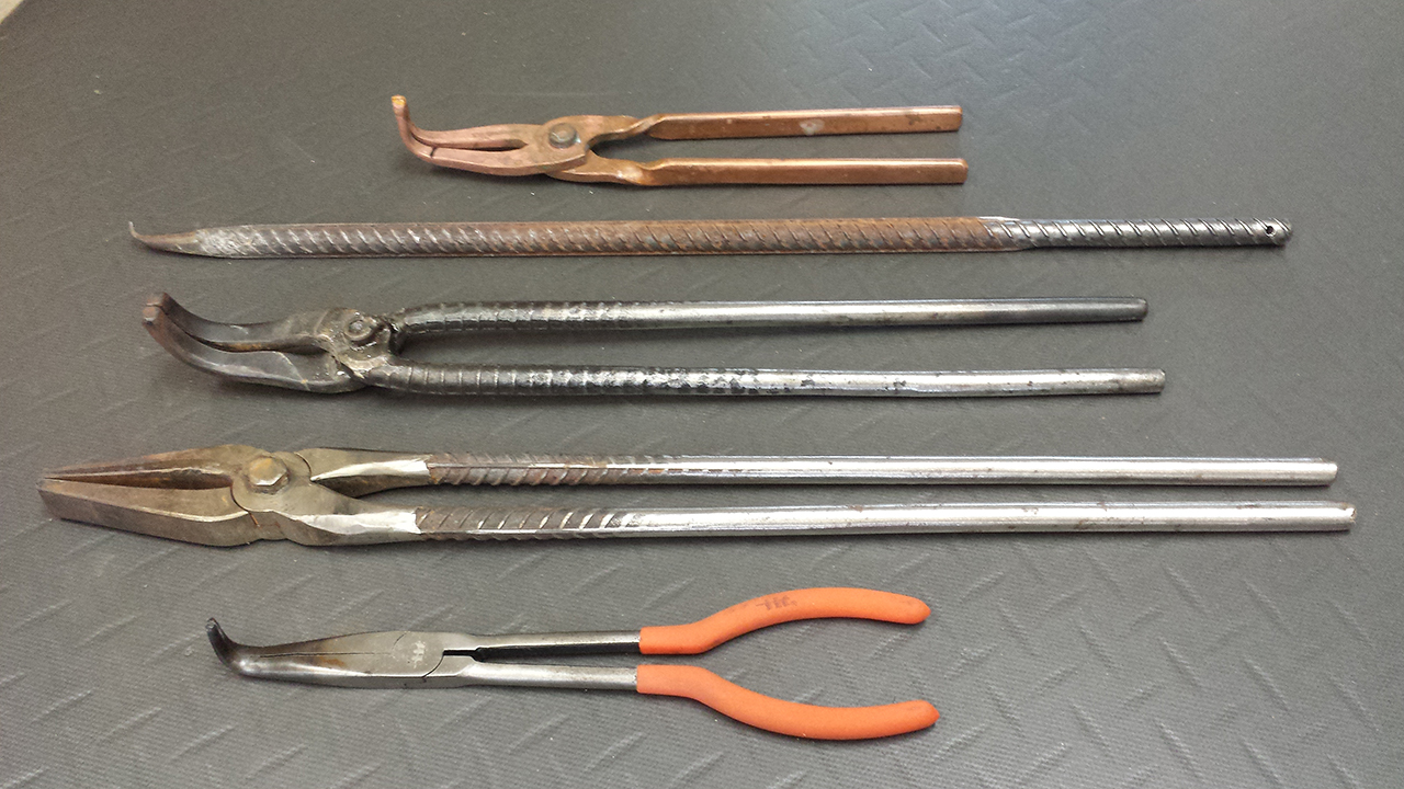 Fig. 5:  From top, heavy copper pickle tongs,  billet turning hook, right angle blacksmith tongs, duckbill blacksmith tongs, small right angle tongs.
