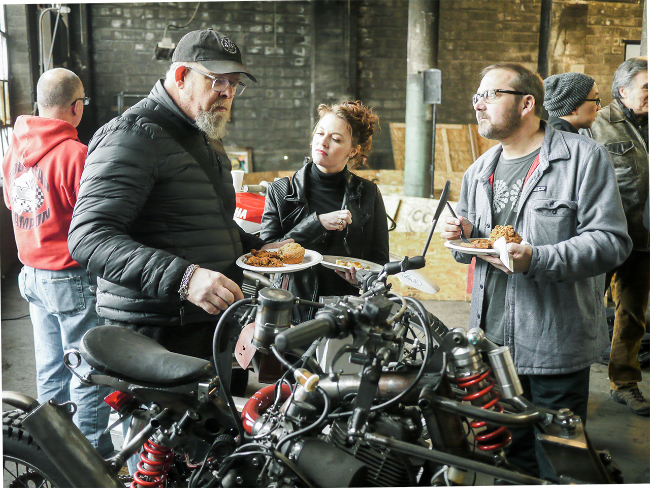 Food and talking about motorcycles go together well. Alan Lapp (left) explains the workings of his creation.