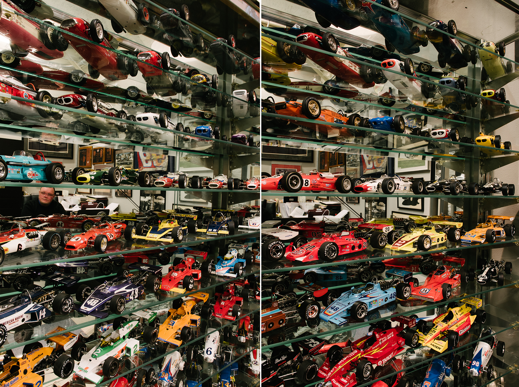 A display of 100-plus Indy car die casts line a wall.