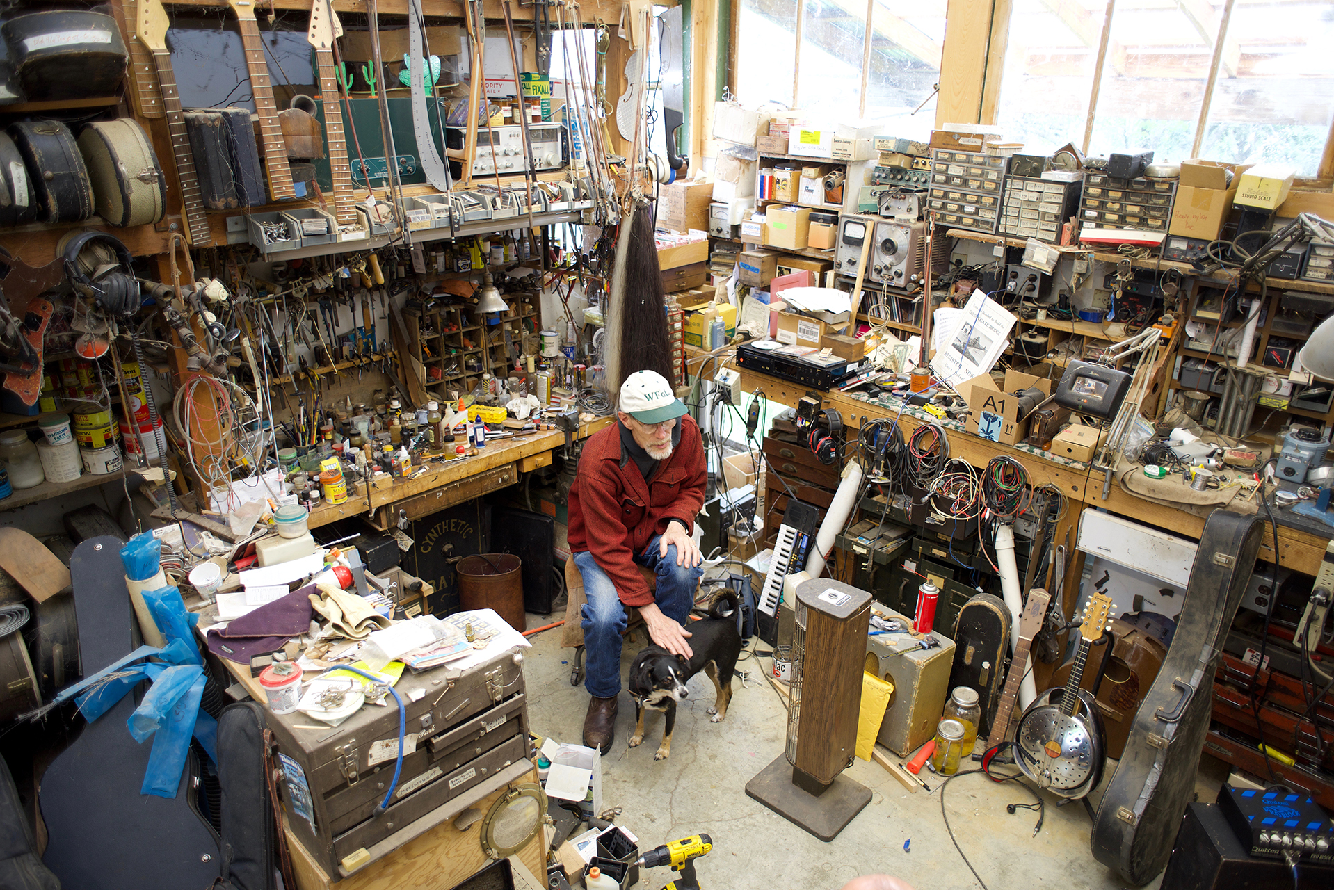 Luthier Keith Cary in his workshop surrounded by a lifetime's worth of instruments, tools and supplies.