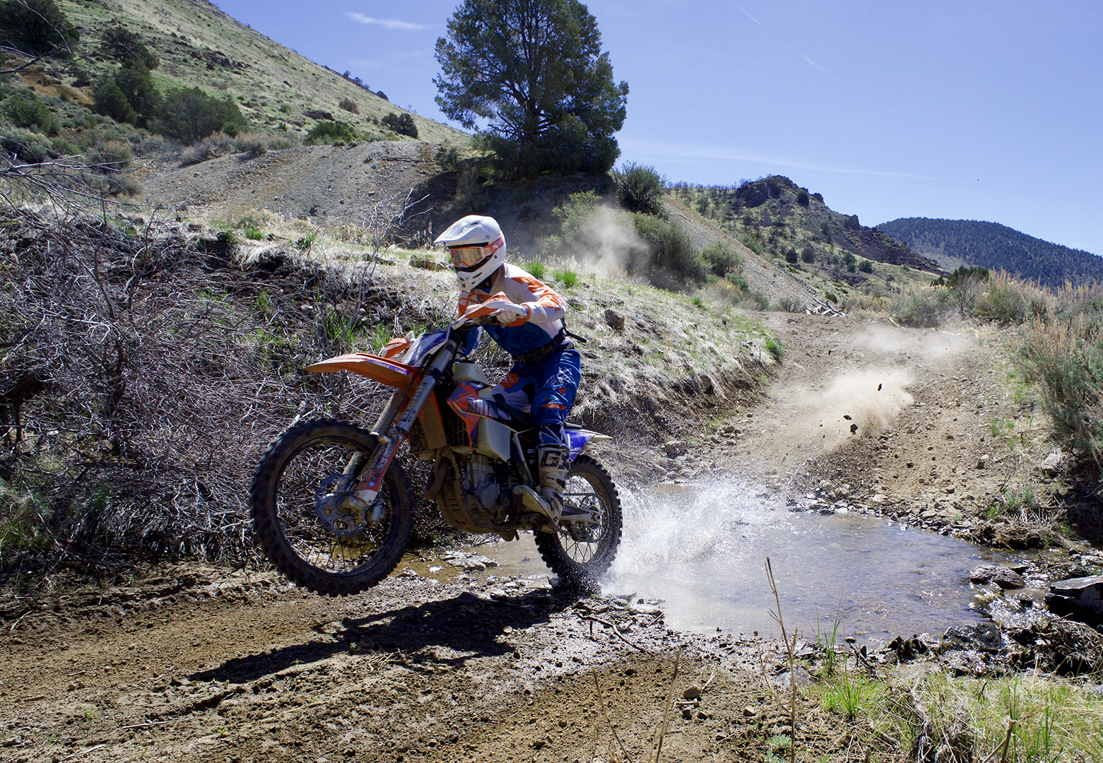 Five-time winner Ross Neely wheelies through the creek in Seven Mile canyon on the first lap headed for the steep climb up to the cemetery.