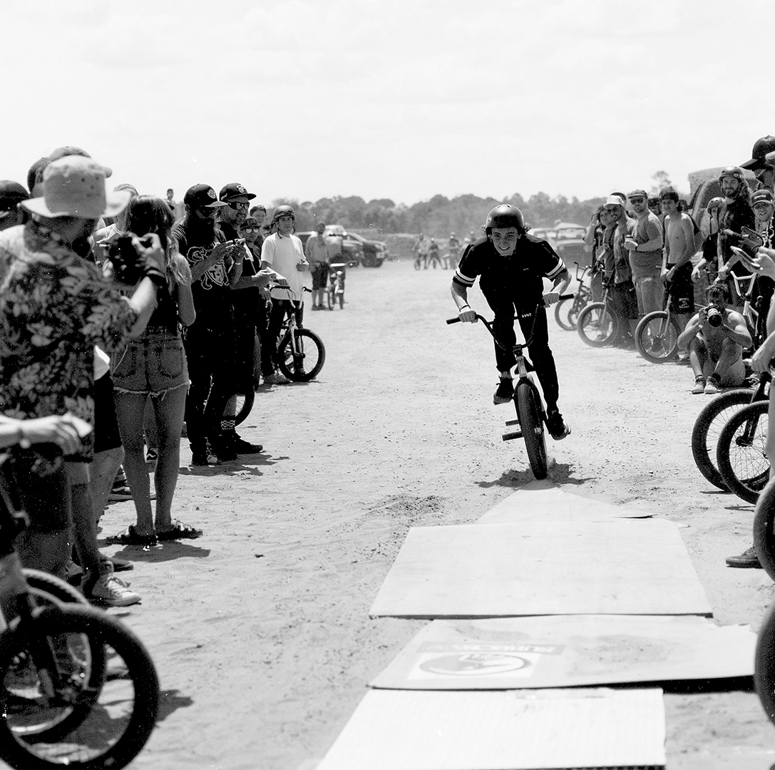This is Preston Okert. His effortless style on a bike is his secret weapon and the chasm jump at Swampfest was right up his alley, here you see the crowd behind him at the starting point for the jump and this loose scrap wood is the final few feet before taking off the lip. I shot this with a Hasselblad 503cw 150mm F4 on Fomapan 100 film.