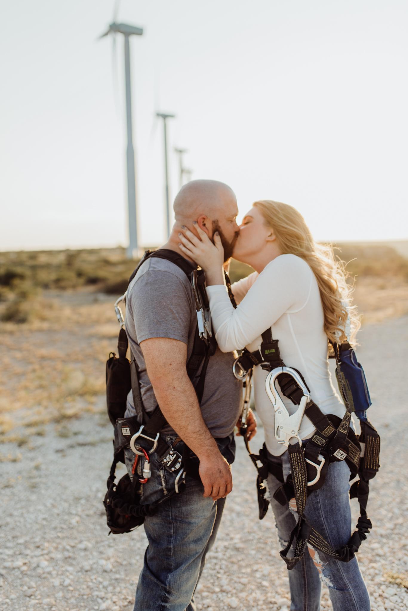 Engaged couple kissing under windmills