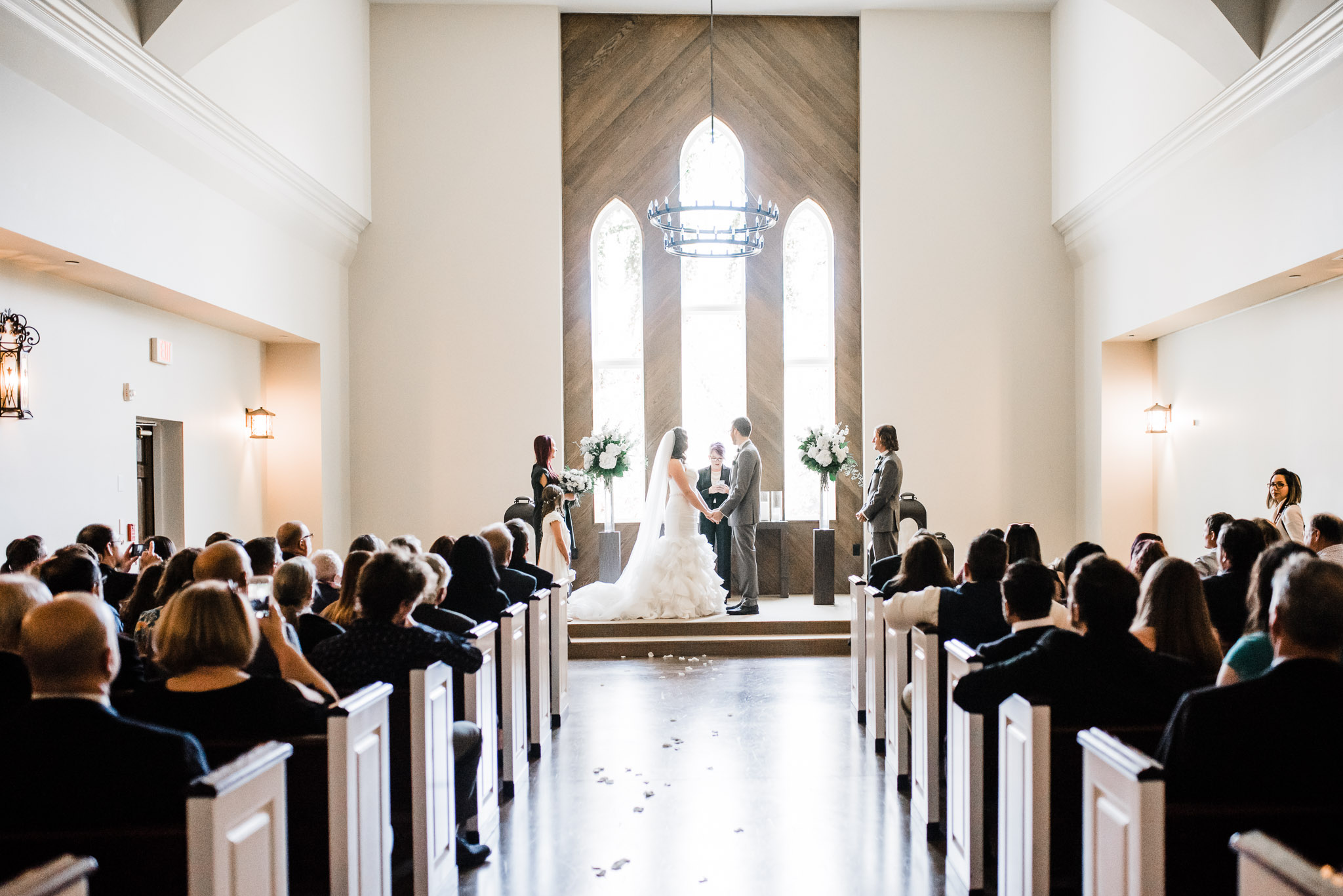 Wide shot of the bride and groom as they read their vows