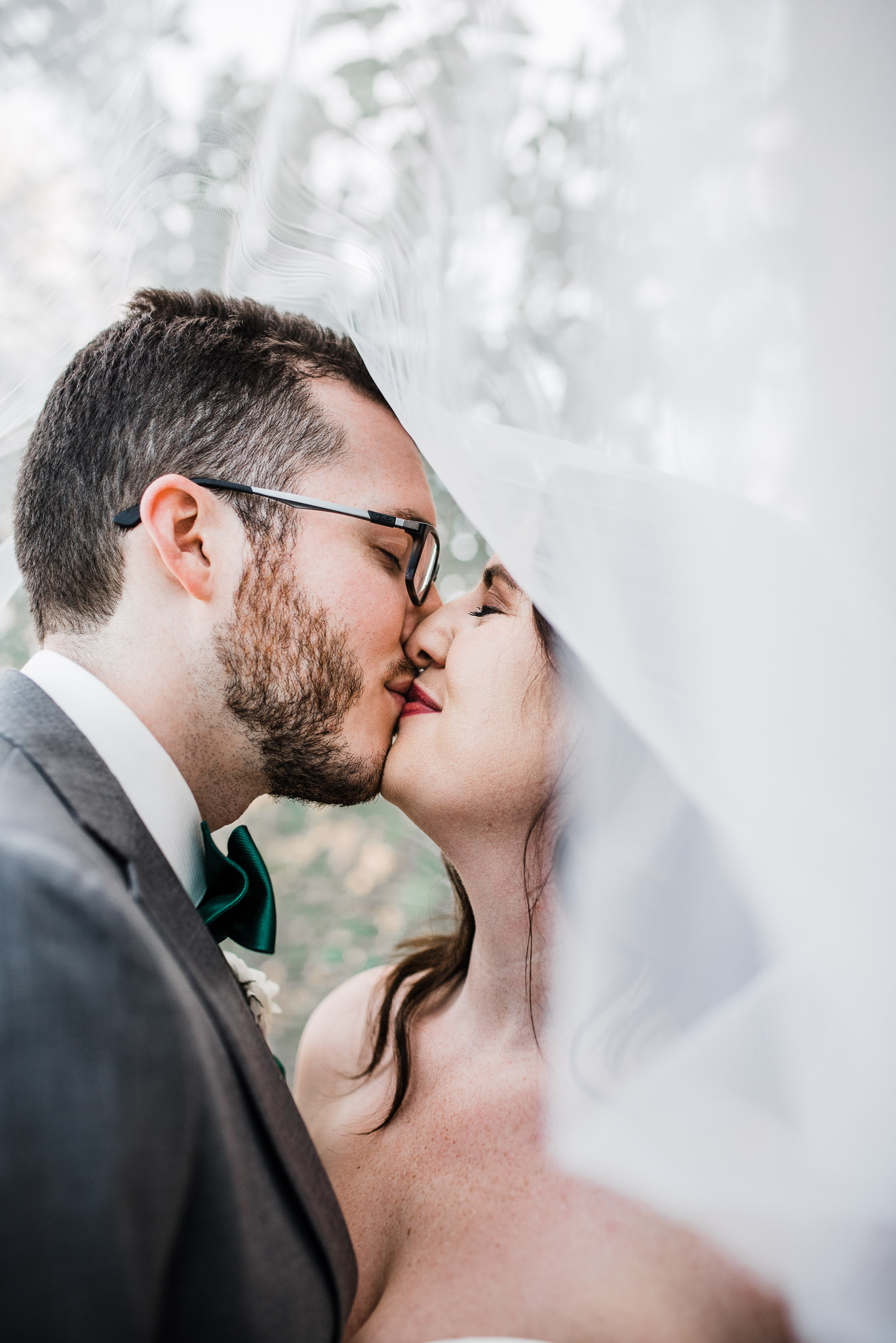 Bride and groom kissing inside the veil