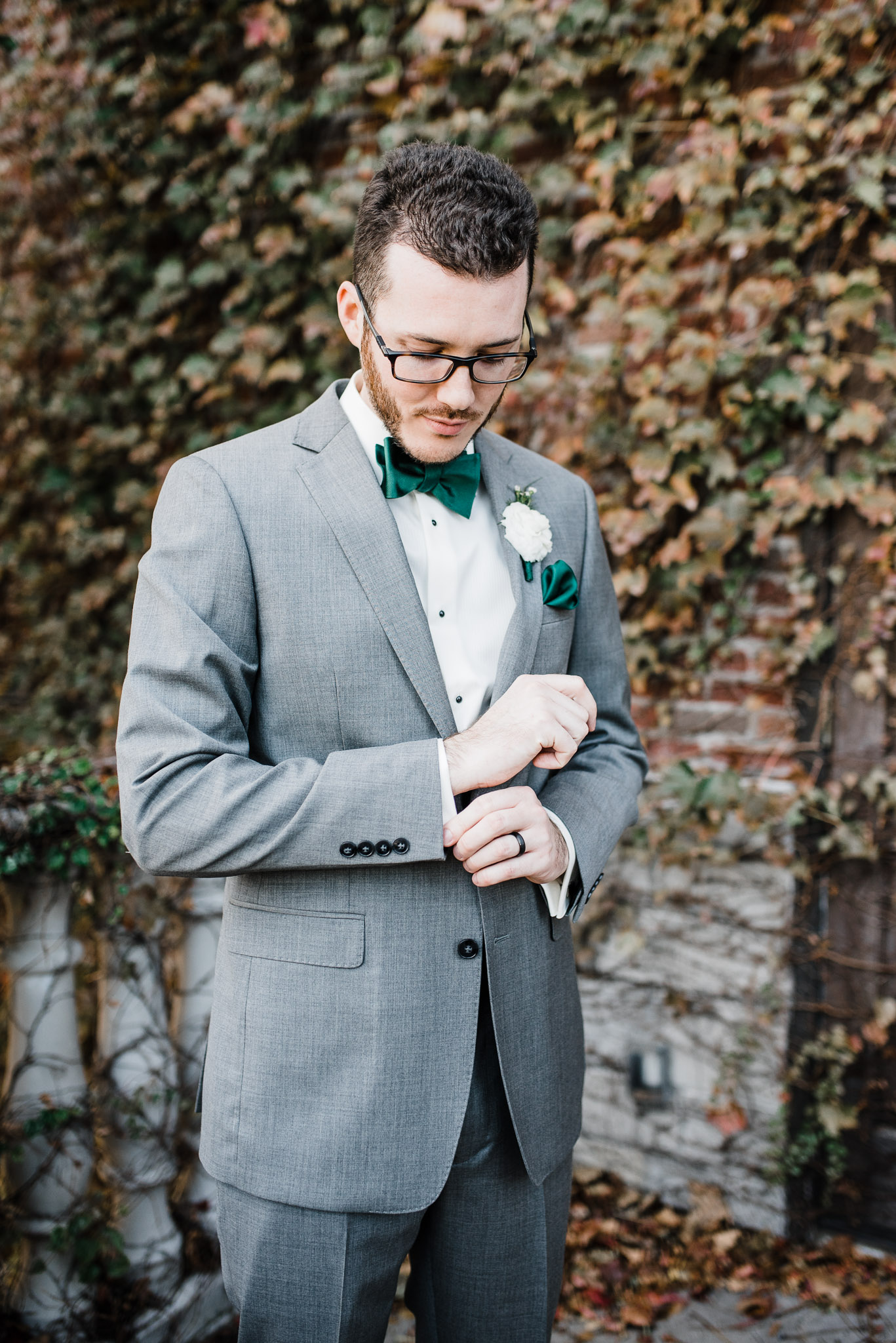 Groom stands to get his suit photographed