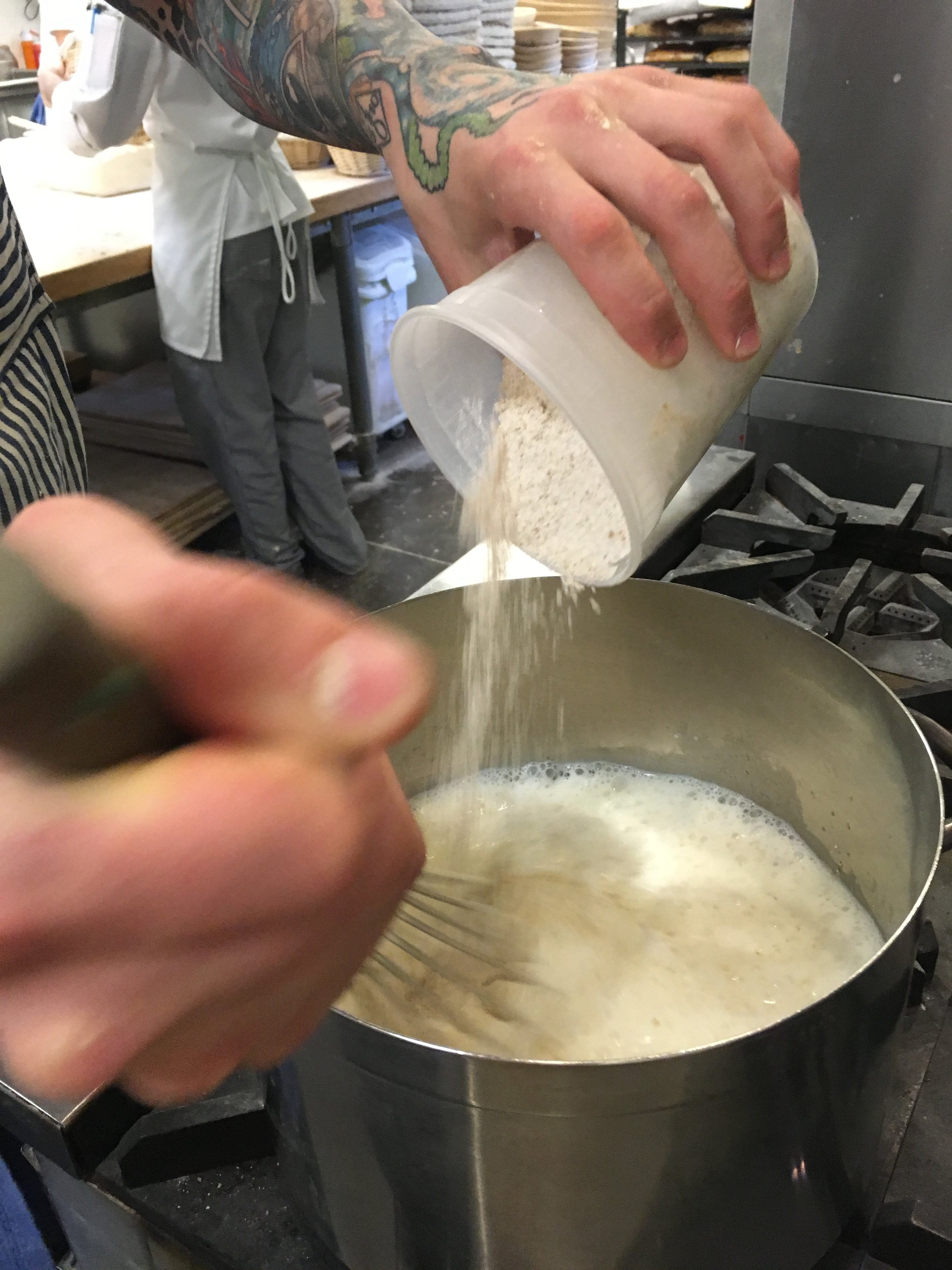 Whisking flour and salt into scalded milk and butter