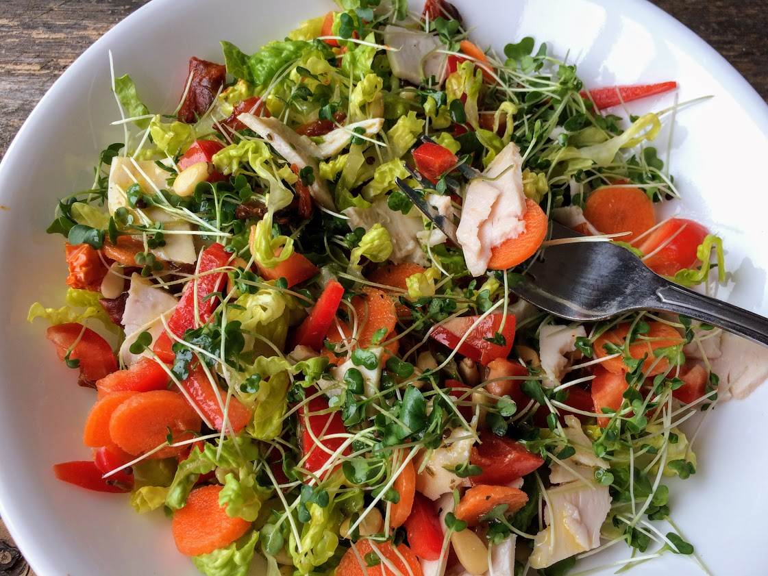 Lettuce, microgreens, carrots, bell peppers, turkey, and pine nuts in this salad.