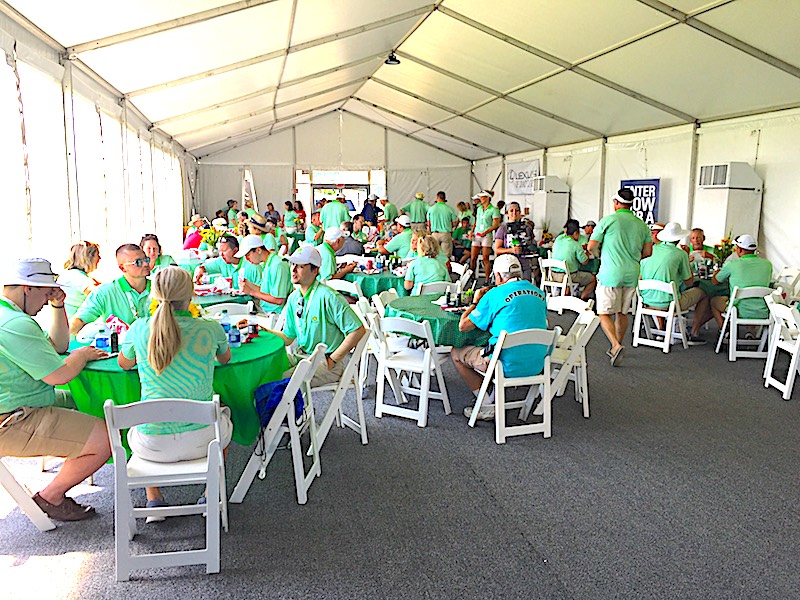 Volunteer marshals gather for lunch in a large hospitality tent before or after a shift.