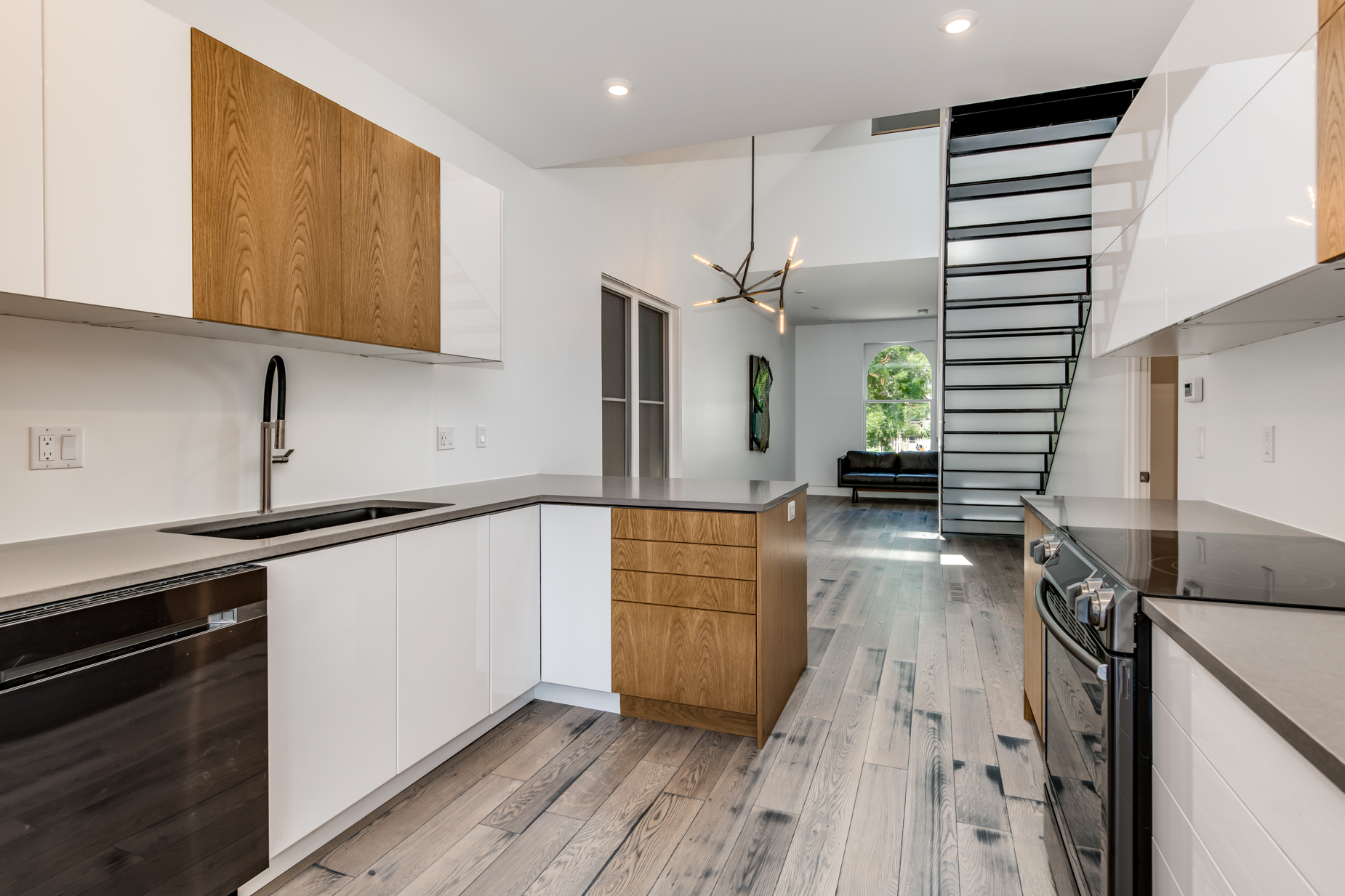 Custom kitchen in natural White Oak fabricated by PAPER AIRPLANE. Staircase utilizes eco-resin risers engineered by 3Form.