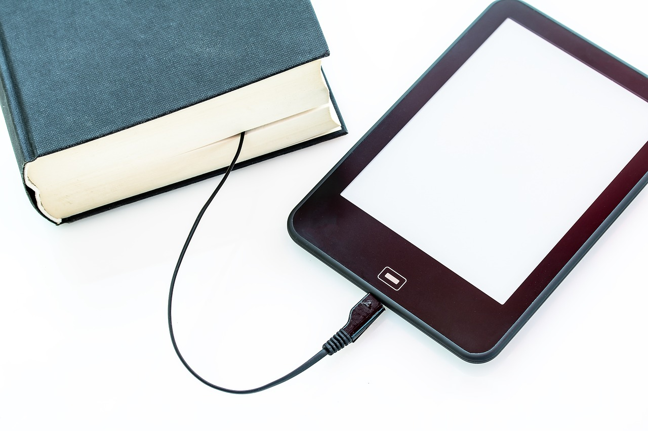 eReader being charged by hardcover book