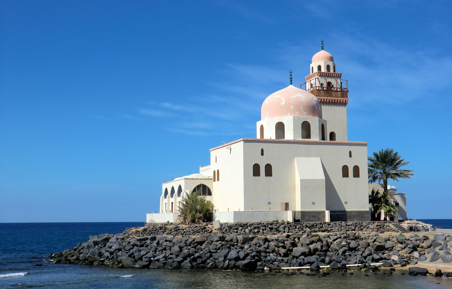 A white mosque on a rocky outcropping jutting into the sea.