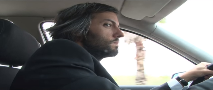 A man driving in a car staring at someone in the passenger seat out of the corner of his eye