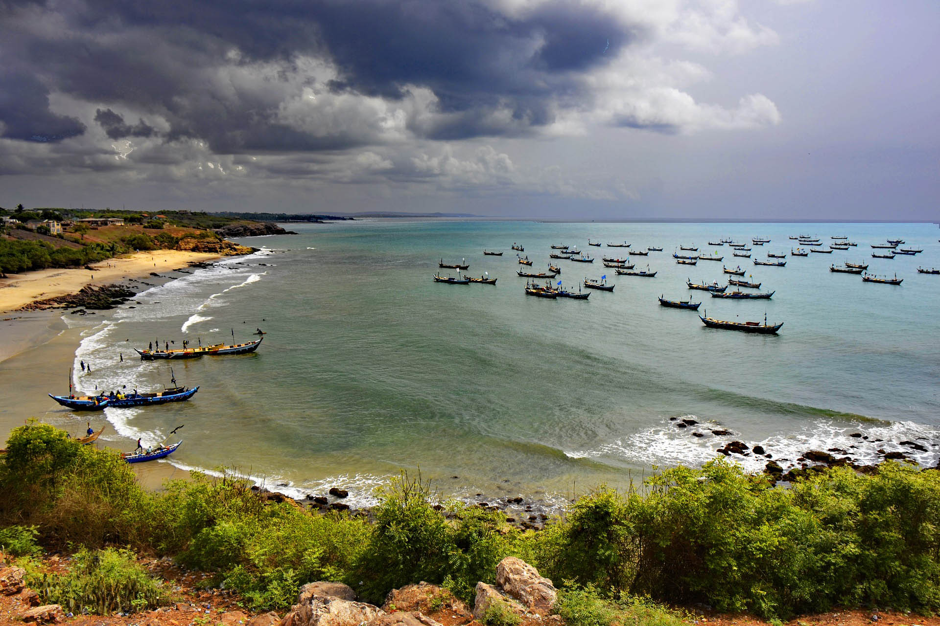 A beach & sea with small boats upon it. A stormy sky appears overhead.