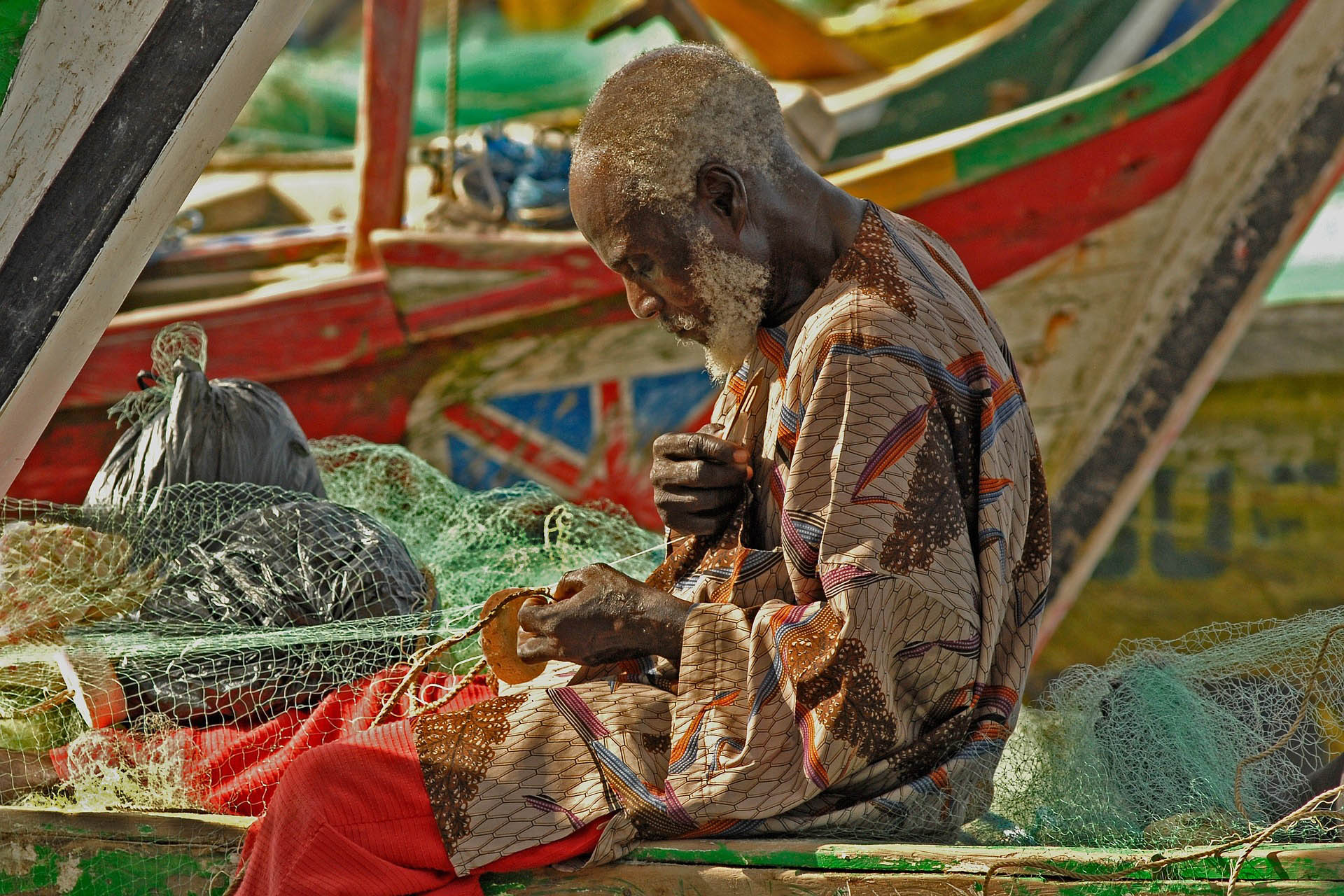 A Ghanaian fisherman repairing a net while sitting on his boat on the beach.