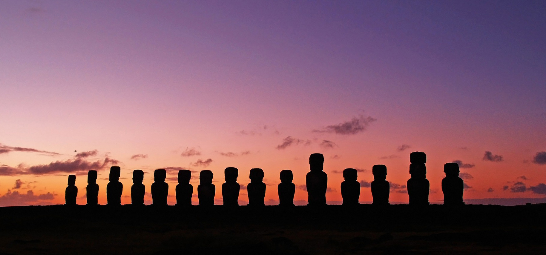 A sunset view on Chile's Easter Island with a line of the giant human-esque stone statues shown in silhouette in front of a purplish apricot-colored sky.