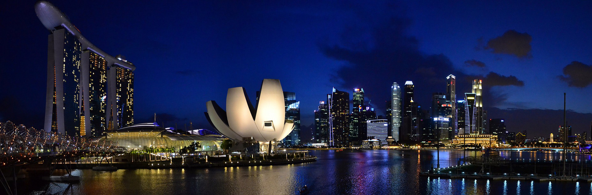 The nighttime skyline of a city on the water. Two unique structures can be seen on the left. The first is comprised of 3 flat buildings joined together at the top by a curved object which looks like the underside of a submarine. The other structure is a light, silvery object lit up in bright white light looking like a cupped robot hand with 5 fingers squared off at the ends.