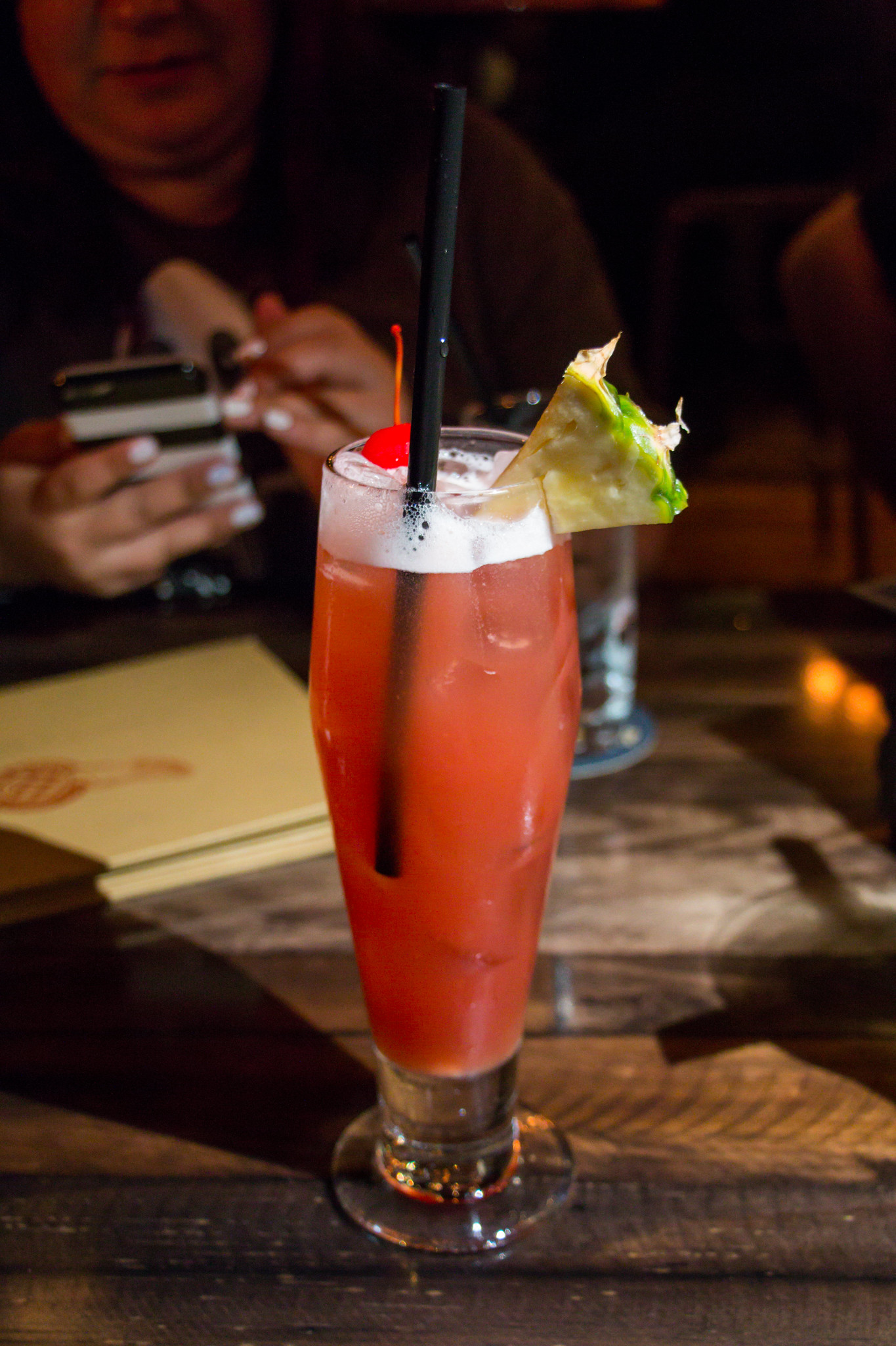 A reddish/pinkish drink served in a tall glass with a pinkish foam on top along with a pineapple & cherry garnish.