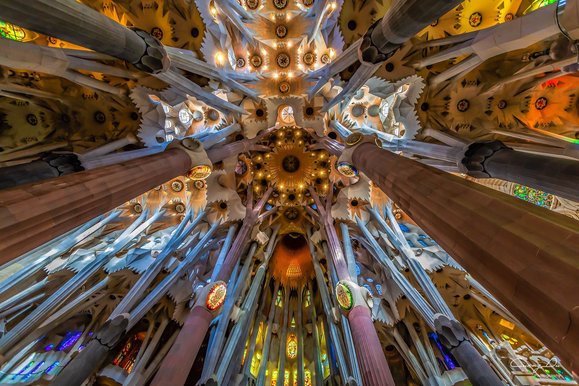 Inside the famous Sagrada Familia cathedral in Barcelona looking up at the carved ceiling & the glorious colored stained-glass windows.