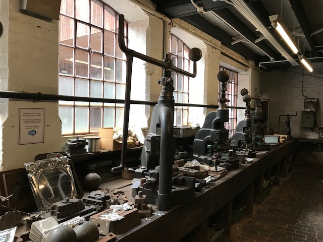 This room was full of workers using the fly presses to stamp and pierce small decorative items.