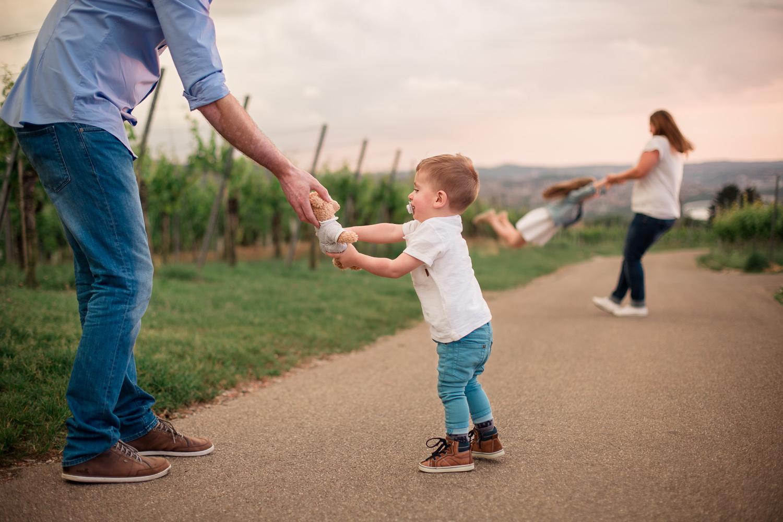 Sandra Ruth Fotografin Familie Stuttgart  Vater und Sohn halten Teddy Mutter spielt mit Tochter.jpg