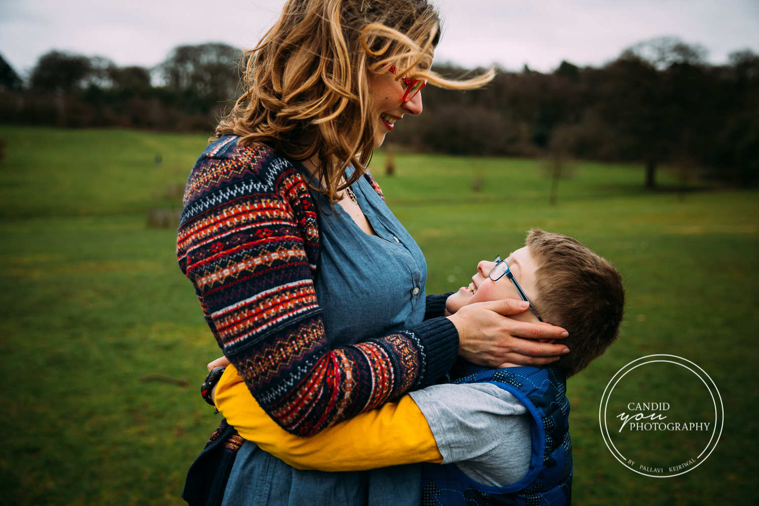 mum holds son's face and looks on with love and son reflects expression of love